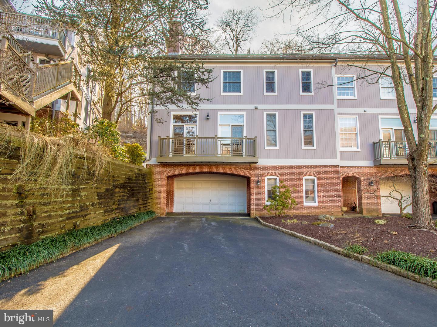 Extensively renovated 3 story end unit townhome in the very desirable gated community of Rockland Mills.  Enter this beautiful and meticulously cared for townhome through the spacious tile foyer.  This floor includes a room with ample closet space and is perfect for an office, den or workout room. Walk up the wide wood staircase and you will be greeted by an open floor plan with the great room that is open to dining area and kitchen.  The great room features a corner fireplace, gleaming hardwood floors and French doors that bring in abundant natural sunlight and lead to a large deck.  Here you will love entertaining or relaxing while taking in the view of the terraced hillside and woods.  Beautiful custom kitchen boasts gourmet stainless steel appliances including brand new Sub Zero refrigerator and Kitchen Aid double ovens, warming drawer and cooktop as well as granite counters, glass tile back splash and inset cabinetry. Adjacent to the great room is a lovely sitting room with French doors that lead to a standing balcony.  This room, with an adjoining full bath, can easily become a bedroom on the main floor by adding doors. On the third floor an impressive master suite and a second bedroom with en-suite bath await.  The master suite features a private balcony, three closets and luxurious bath including large seamless glass shower, spacious vanity with granite counter and nook with glass shelving.  Additional features include a 2-car garage with driveway for additional parking, laundry on the the bedroom level and all baths that have been fully updated. Located on the banks of the Brandywine River you will enjoy nature while being conveniently located only minutes from restaurants and shopping. This move-in ready, beautifully appointed townhome is a must see, and all furnishings can be negotiated.