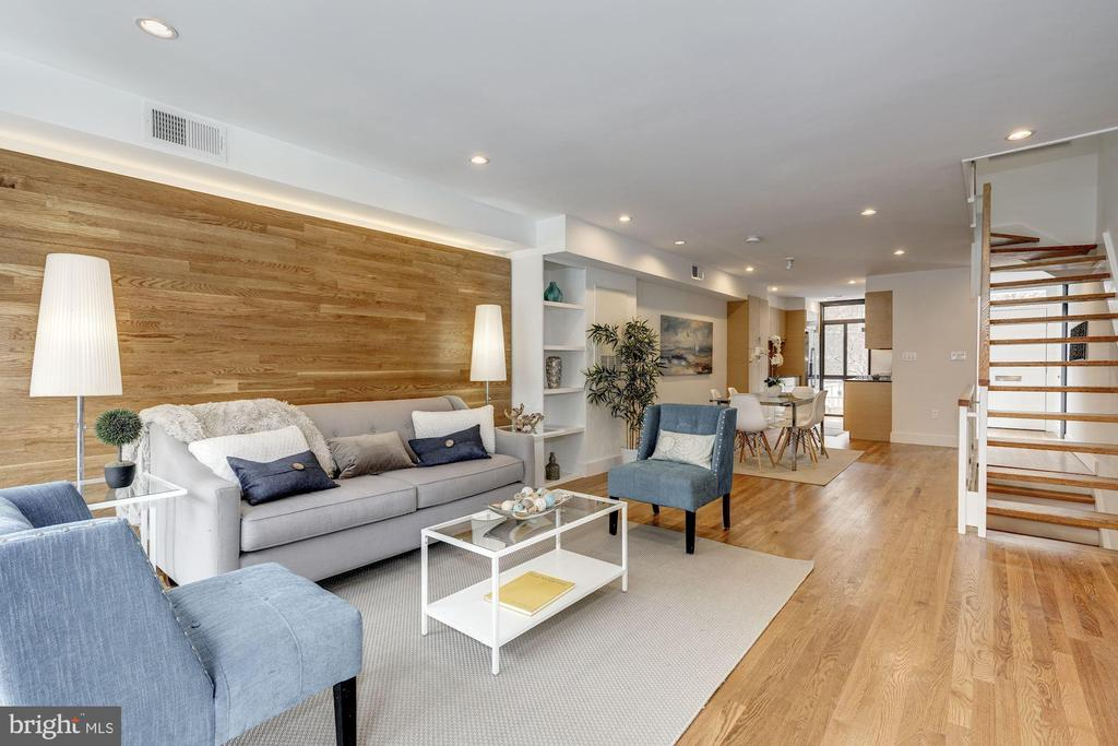 Spectacular Renovation of a Stylish and Sophisticated 1960's Townhouse. This 3 level brick end unit is located where distance to metro can be measured by yards instead of miles! The Wharf is an 8 minute stroll. Nationals Ball Park & Audi Soccer Stadium are close neighbors. 3 large bedrooms, 3 full designer bathrooms, a rare main level powder room, a family room with full wet bar & walk out to private flagstone patio provide for all the luxury living you now expect.  The open floor plan and floating staircase are accentuated by the sunlight derived from floor to ceiling windows on each level. Flawless hardwood floors enhance the beauty of this classic contemporary design.  The sleek, architect designed, kitchen is opulently appointed with access opening from foyer and boasts Quartz counter-tops, Carrara Gioia marble back splash, Destiny Line Ultracraft Cabinets, Bosch appliances & an exterior vented exhaust range hood.Highlights include: Full renovation including plumbing, HVAC units & electric panel/Pristine oak hardwood floors on both 2nd & 3rd levels/fully tiled lower level/ 2 zone HVAC system/Copious cabinets & closets/Storage unit under stairway/Abundant built-ins/Full sized washer and dryer on 2nd floor. Bonus: one dedicated parking space!