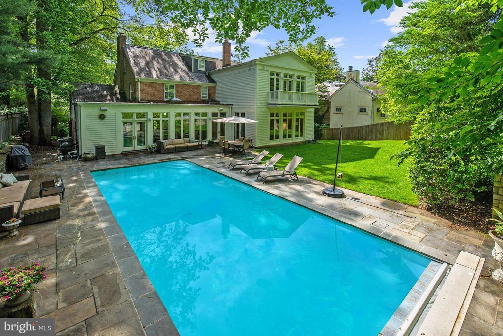 Price Adjustment and Open House Sunday March 10 2-4!  Elegant and expansive Spring Valley home with over 5,700 square feet of living space. The finest outdoor setting in Northwest DC!  Amazing backyard with heated pool and lavish flagstone patio! This stately home is much larger than it appears in photos. This 5 bed, 5.5 bath home features banquet sized rooms, high ceilings, floor to ceiling windows, solarium with double french doors leading to backyard oasis, radiant heated floors, finished lower level with home theater and recently renovated rec area. The second upper-level includes a bedroom,  full bath and extra living space perfect for an au-pair or guests. This fabulous home is perfect for both entertaining & everyday living! Must See!