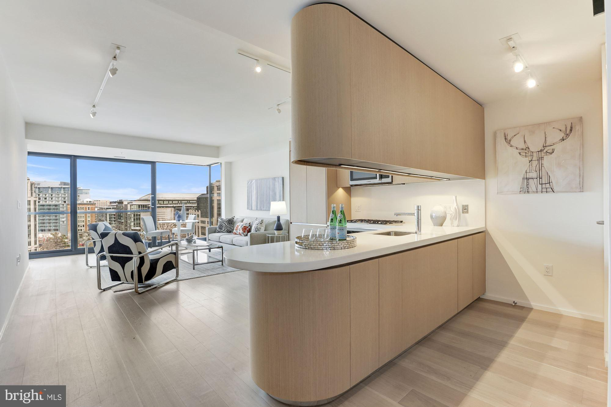 This penthouse-level luxury condo in the heart of DC~s City Center features over 800 square feet of living space with 1 bedroom and 1 full bath. Complete with hardwood floors, sleek contemporary finishes, and views of Downtown DC through the expansive floor-to-ceiling windows, this light-filled unit is move-in ready and comes with an assigned private parking space the attached underground garage. Building amenities include concierge services, security, a full-service fitness center, club room, as well as proximity (2 blocks) to the metro and the best shops and restaurants the city has to offer. Showings by appointment only.