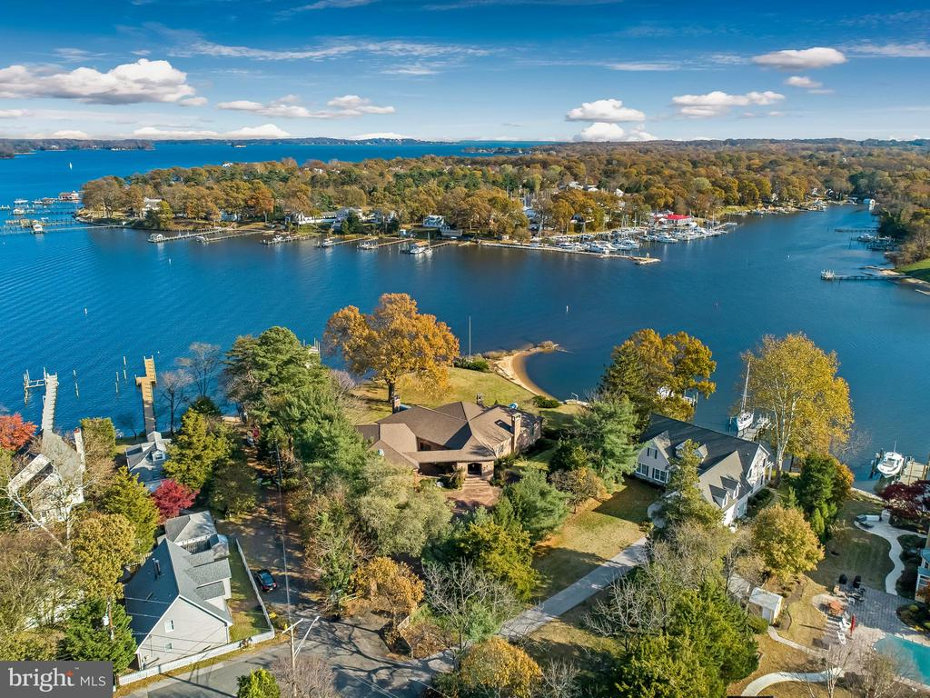 Stunning waterfront on BREEZY POINT; This 7,000 square foot custom home is on 1.26 acres with 400 feet + of water front, two piers and boat lift. Water depth and pier are suitable for yacht. Sandy beach. Enjoy exceptional views and privacy. Luxurious quality to include marble and hardwood floors, 10 ft. coffered ceilings, beautiful trim work through-out and solid wood interior doors. All brick exterior and driveway. First floor kitchen with professional 6 burners Viking stove, huge island, wine cooler, & French doors leading to 45 FT X 12 FT balcony w/custom tiles over looking this incredible property and the Magothy River. 27 Ft long formal dining room with 3 layered tray ceiling and built in light. Incredible view of the river from the stunning rows of windows in the living room & custom fireplace. A true Master suite with huge master bath and walk-in custom closet and another  five bedrooms, each with a full bath. The ELEVATOR will take you to the lower level walk out Great room w/fireplace and another large professional kitchen set up for your fun entertaining w/French doors to a 40 X 14 custom porch. Two private offices, seven full baths, two half baths. Four car heated garage and carport large enough for 3 cars, two laundry rooms, 4 zone heating system, wine cellar, two extra refrigerators and freezer and irrigation system. Whole house generator runs everything in home. Huge storage area. Great home for entertaining and all year living.