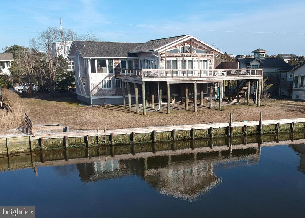 This timeless Bayfront home with Nantucket inspired architecture creates an idyllic waterfront residence. The spacious open floor plan with soaring ceilings and window lined walls maximize panoramic views of the water and natural wetlands. This impressive property boasts 112 feet of bulkheaded waterfront which offers easy access to the Indian River inlet. Featuring a desirable floorplan with a master suite on the top floor as well as a second bedroom or office and 3 bedrooms and 2 full bathrooms on the floor below. This home is perfect for comfortably entertaining with plenty of space both indoors and out with a huge second living room with a wet bar and an expansive bayside deck. This home offers the convenience of an attached garage as well as a ground level pantry with a second refrigerator and sink. Desirably located on a quiet street in a North Bethany community with a private beach, tennis courts and a marina, this home is offered fully furnished.