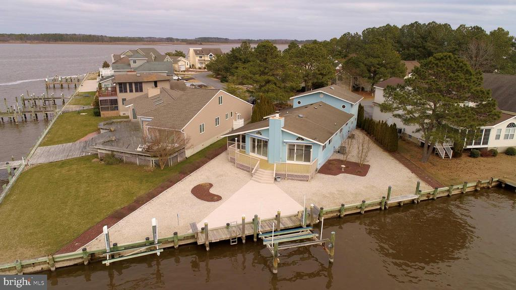 This well maintained home offers fantastic views of the St. Martins Neck River. Perfect property for the avid boater and fisherman. A 114' 2 year old bulkhead wraps around the front of this property and has 2 docks and 2 lifts, one 8,000 lb and one 3600 lb capacity. The views from the front yard, deck,living room, dining and kitchen are second to none. This home offer an open floorplan, large  lkitchen with island, adjoining open dining room , living room with fireplace and 4 bedrooms and 3 baths which includes a first floor master suite.Situated in Ocean Pines which offers a complete package of amenities plus a public library, Post Office and its own fire company. 5 minutes to shopping, restaurants and medical facilities.