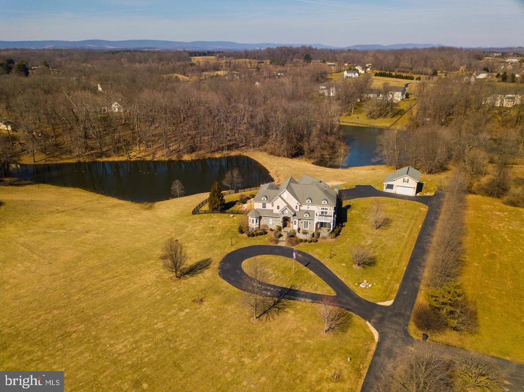 ***PRICE JUST REDUCED BY $50K***RESORT STYLE HOME-FEEL LIKE YOU ARE ON VACATION YEAR ROUND-GORGEOUS CUSTOM BUILT HOME ON 4.7 ACRES WITH OVER 7200 SQUARE FEET OF FINISHED SPACE IN SOUGHT AFTER ASHLEY SPRINGS COMMUNITY-IN GROUND POOL WITH HOT TUB, LARGE PATIO AND DECK-FENCED REAR YARD TO PRIVATE POND GREAT FOR FISHING OR CANOEING-GOURMET KITCHEN WITH VIKING COOKTOP, SUB ZERO REFRIGERATOR, TRASH COMPACTOR, WINE COOLER, 2 SINKS & HUGE ISLAND-KITCHEN OPENS TO STONE PATIO-MAIN LEVEL MASTER BEDROOM SUITE WITH GREAT VIEWS OF POOL, POND AND TREES-LUXURY MASTER BATH WITH JACUZZI TUB, SEPARATE SHOWER AND DUAL VANITIES-CUSTOM BUILT-INS THROUGHOUT WITH ARCHED DOORWAYS-LARGE FAMILY ROOM WITH GAS FIREPLACE AND ACCESS TO CUSTOM DECK-UPPER LEVEL HAS 4 SPACIOUS BEDROOMS AND 2 FULL BATHS WITH ITS OWN UPPER LEVEL FAMILY ROOM-FULLY FINISHED LOWER LEVEL WITH FULL KITCHEN, WORKOUT ROOM, 6TH BEDROOM, FULL BATH, DEN/OFFICE AND STORAGE-OVERSIZED 3 CAR ATTACHED GARAGE WITH GREAT STORAGE-DETACHED 2 CAR GARAGE WITH WORKSHOP AND FULL ATTIC FOR STORAGE-GREAT PORCH ON DETACHED GARAGE TO SIT AND ENJOY YOUR PRIVACY AND POND VIEWS-BILLIARD TABLE, SONY THEATER SYSTEM, BOW-FLEX FITNESS EQUIPMENT AND POOL SIDE WHITE FURNITURE ALL CONVEY-TOO MANY ITEMS TO LIST-THIS IS A MUST SEE FOR ALL YOUR PICKIEST CLIENTS