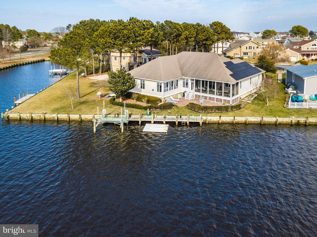 Imagine living in this Luxurious waterfront home with breathtaking views of spectacular sunsets over the canal, bay. An extraordinary One Level living home boasts  over 3600 square of exquisite living space with boat dock and 8,000 lb boat lift  and over 100  feet of bulkhead with Direct access to the Bay!!! .  This 4 bedroom 2.5 Designer Baths, Den, Oversize bonus room is move in ready for your summer enjoyment.  There are glass sliders and a wall of windows to optimize all the water views off living room, great room, kitchen and breakfast room.. Entertaining in this home will be effortless with great room to enjoy the warmth of the gas fireplace, full entertainment system with built in TV and surround sound located off expansive kitchen and breakfast bar seating, two separate dining areas, upgraded cabinetry with under mount and over mount lighting. This dazzling kitchen features both granite countertops as well as teak designed bar seating. The soft Caribbean feel of paint colors are showcased throughout the home. After a full day of boating, fishing or sunning enjoy some relaxation in the most amazing waterfront Master Suite and Master Bath..  This home has many  enhancements  throughout including heated tile master bath floors, Air Jetted tub, separate make up vanity, newer carpet, cortex flooring in kitchen, owned solar panels,  baffle geothermal heat and air, newer heat pump for bonus room, 2x6 construction on exterior walls, expansive screen porch with vinyl tech windows, pull down attic, leaf gutter guard, Lawn Irrigation system, wired for security system, surround sound system oversize 2 car garage, paved driveway to accommodate at least 6 cars. One level Paradise Living at it~s Finest Awaits your arrival! Call now for your private showing