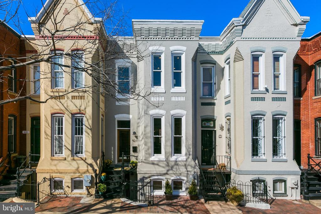 Originally built in 1890 and recently renovated with precision and care by Dogwood Restoration, this 4-bedroom federal brick home is sited on one of Shaw's prettiest and serene blocks. The main level features open concept living and dining areas flooded with natural light. The light is accentuated by the floor to ceiling wall of glass in the rear of the kitchen that opens to the rear garden and secure parking. Upstairs there are three bedrooms including a beautiful master bedroom featuring lofted ceilings, an elegant master bathroom with dual vanities, marble mosaic flooring and a frameless glass shower enclosure. There is also a second full bathroom upstairs located between the second and third bedrooms. The lower level is perfect for an au-pair or in-law suite and consists of a fourth bedroom, a wet bar (kitchenette) and a third luxurious full bathroom.