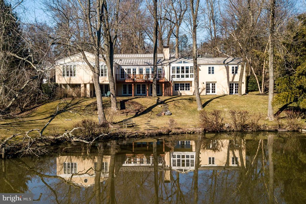 This luxury Riverside retreat captures an always-changing panorama of Carnegie Lake: a Great Blue Heron perched in a majestic tree, Princeton crew besting yesterday's time, an immature eagle searching for fish. Renovated by noted local architect, Max Hayden, this splendid home sings with natural light, hardwood floors, and views for days. A cathedral entry gallery opens to a stunning kitchen and dining room, where French doors lead to the deck and its lake vista. Custom cherry cabinets, slate fireplace, and a granite island contrast warmly with top-line stainless appliances that include a 6-burner Dacor range. A 2nd fireplace and a bay window encourage lingering in the vaulted living room. 2 bedroom suites on this floor include the serene master, with spectacular sweeping lake views and a limestone bath. The flexible lower level is no less compelling; a fireside family room opens to a covered patio, 2 view-filled bedrooms, an exercise room, and granite-trimmed bath. Ample storage is found in an equipment room with lakeside access and 2-car garage.