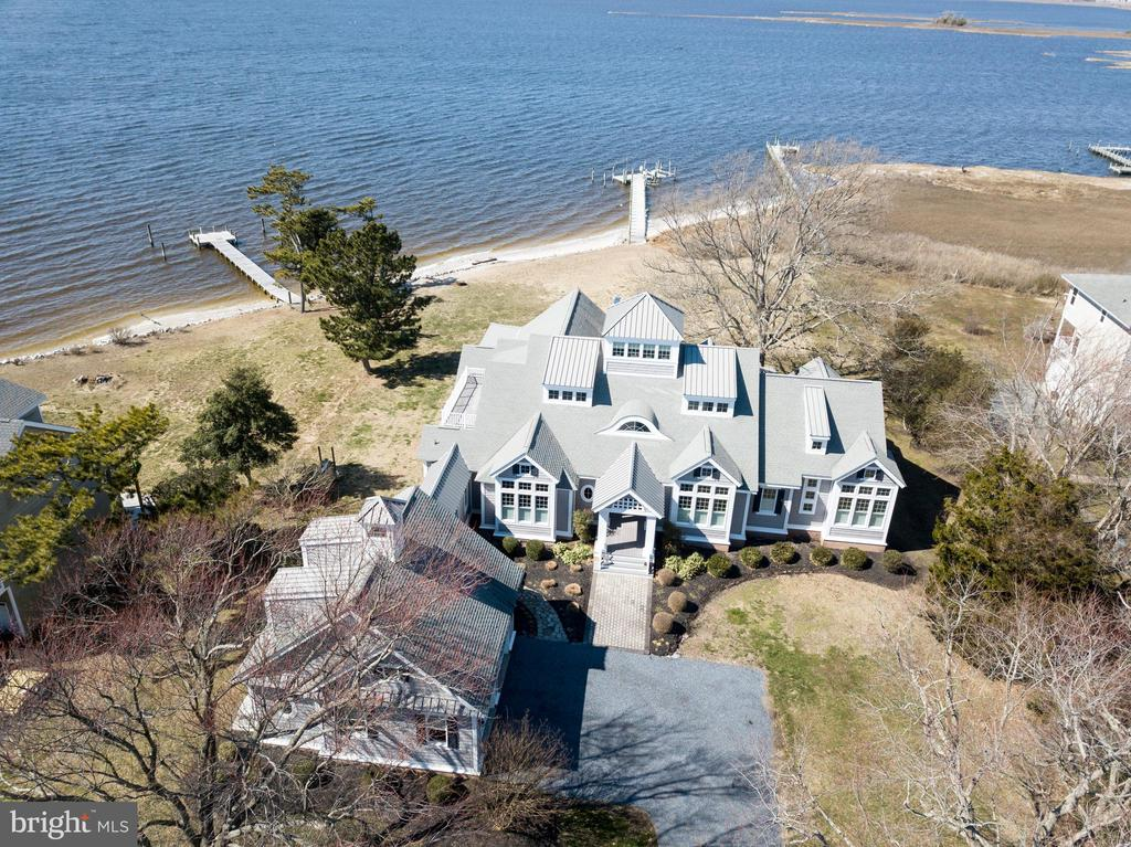 This exceptionally beautiful approximately 5,145 sf home was designed by Becker Morgan/Chris Pattey and is situated on 2.95 waterfront acres with western exposure on Newport Bay/Spence Cove with spectacular views and sunsets.  A 125 ft pier with water/electric and 10,000 lb and 2,500 lb boat lifts and fish cleaning station is included.The sunny kitchen, featuring Kitchenaid appliances, a 6 burner gas range, warming drawer and a Frigidaire double refrigerator-freezer, overlooks the great room which features beautiful views, two fishing rod ceiling fans and a wood burning fireplace.  You can enjoy the stone floor, wood burning fireplace and ceiling fans in the screened in porch.The first floor master suite includes a gas fireplace and ceiling fan.  The master bath is equipped with double sinks, a three head shower and an air jet tub.  The second floor features two bedroom suites, each with full bathrooms and private decks.  There is an observation room on the third floor.  The oversized two car garage with oversized garage doors can accommodate a full size four door pick up and has an unfinished storage area on the second floor.The quality construction features include brick/block foundation, upgraded spray foam insulation w/batt insulation, Anderson Series 400 windows/doors throughout, two 5 ton and two 1 ton water furnace Envision geothermal systems w/steam humidifier, no maintenance CertainTeed vinyl siding, private well/septic , 10 ft first floor ceilings and 9 ft second floor hallway ceilings,  hardwood floors in the great room, kitchen, dining, office, entry, eat-in area, power and tower room; carpet in the media room and bedrooms; and tile in the bathrooms.  Additional items included are a 20 KW back up generator, water softener, Burglar/Fire Alarm system, outside shower, duck blind permit and a 25 ft by 25 ft (625 sq ft) storage building built in 2007 featuring a heat pump, 2nd fl storage area, and two oversized garage doors.Embrace the beautiful waterfront lifestyle offered by this exceptional home!