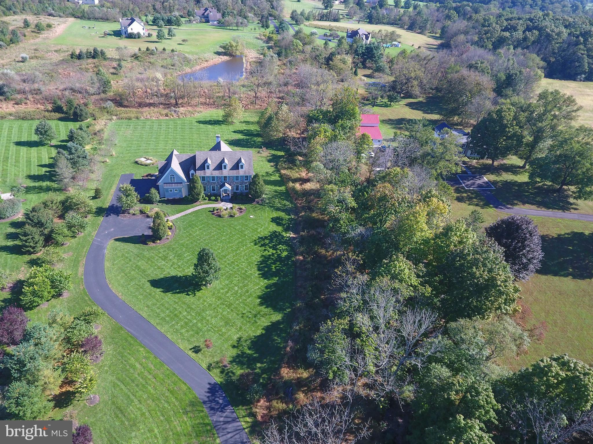 Set majestically back on a long winding driveway, is a gorgeous John Arrow custom-built reproduction Colonial with many luxurious upgrades! Built with the perfect blend of fine craftsmanship, energy efficiency and regard for environmental impact, this upscale and pristine home will please the most discerning buyer! The attention-to-detail is evident with the stone and mixed media exterior and is highlighted by the beautifully crafted portico with slate landing. This curb appeal will beckon you in! Once inside, the reclaimed random width hardwood floors throughout the main level set the tone for quality and warmth in this gracious and open floor plan. The voluminous foyer provides a warm welcome with stunning oak staircase and Palladian door. The spacious formal dining and living rooms flank the foyer with extensive millwork, including wainscoting and are perfect for entertaining. The dramatic double story family room, with numerous windows is crowned by a stunning floor-to-ceiling stone fireplace. Your resident chef will appreciate the gourmet kitchen with custom Cherry cabinetry, granite counters and high-end appliances, including a built-in Sub-Zero refrigerator, Wolf 5 burner gas cooktop, Wolf double oven and Asko dishwasher. The expansive island offers plenty of prep space as well as a venue for casual dining. The many custom interior cabinetry options will promote ease of use and organization. The adjoining breakfast room with vaulted ceiling is sun-drenched and enjoys long-distance views, including the picturesque pond. Plan on dining al fresco on the Trex deck overlooking the nearly 5 acres of land with mature trees and landscaping, allowing privacy and endless possibilities, including a pool. The stately and bright study provides the ideal in-home office with glass French doors adorned with a transom window and is accessible via two adjoining rooms. Up the privacy staircase, you'll find the sumptuous and expansive master bedroom suite which provides an amazing retreat with seating alcove, vaulted ceiling with elegant chandelier and an oversized walk-in closet. The spa-like bathroom features a Jacuzzi tub, a his and her sink vanity with granite counters and a separate water closet with shower. The second level is completed by three generous-sized bedrooms, a Princess Suite with full bathroom and a Jack 'n Jill bathroom servicing the other two bedrooms. You'll enjoy another level of living for your recreational needs with the finished, walk-out basement with numerous daylight windows, a built-in bar, full bathroom and Berber carpeting. Storage is plentiful with the expansive unfinished portion. Home is NAHB GREEN CERTIFIED with reasonable utility expenses. Close proximity to NJ, NY and Routes 202 and 95 and the prestigious Lookaway Golf Club. Blue Ribbon Award Winning Central Bucks Schools. Schedule your private tour today!
