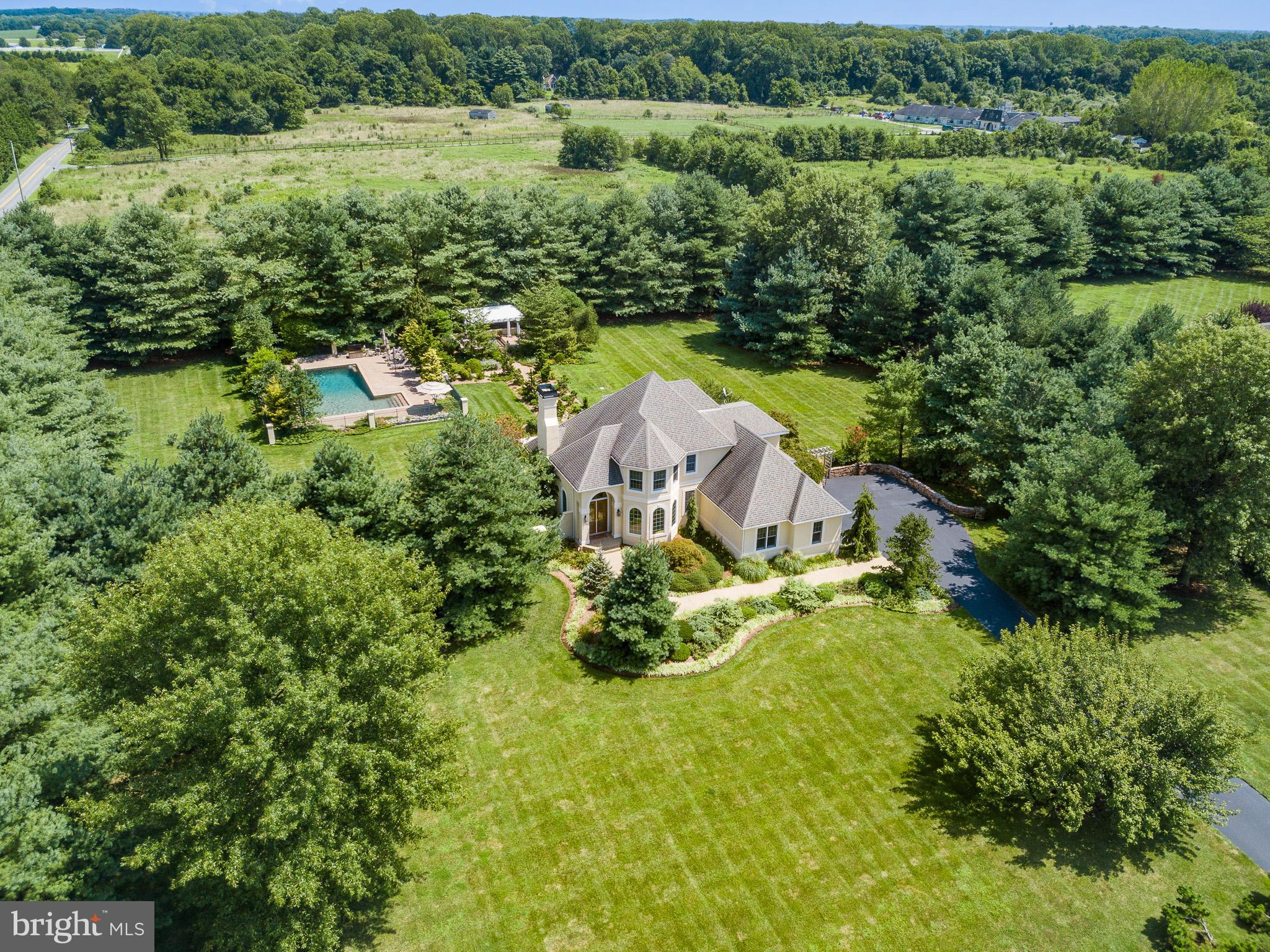 Breathtaking home on Bohemia Mill Pond Dr.! Appreciate custom French country home offering resort-style living on 2-acre landscaped corner lot amid countryside setting. Architecturally alluring 5BRs/4.5 bath beige stucco 3,000 sq.-ft. contemporary home features turret-style front with arched entry and oversized dual-glass front doors. Welcome to sunny 2-story foyer with Palladian window and striking red oak hardwood floors here and throughout home. To right is stunning DR with bump-out trio of Palladian windows and crown molding. Off DR is butler~s pantry, where drink can be mixed and served in moment~s notice thanks to granite-topped glass-pane door cabinets that hold barware and wine refrigerator that keeps bottles at perfect temp! Back of home is volume-ceiling FR with triple window with transom windows, providing cascade of light and uninterrupted views to spectacular outdoor oasis! Maple wood gas FP with ceramic tile hearth anchors room. Gorgeous gourmet kitchen is culinary perfection! Maple cabinets with square marble pulls, tumble marble backsplash and granite countertops with bull-nose finish blend together and complement Jenn-Air SS appliances. Wide countertop serves as bar and backs to bump-out triple window morning nook. Angled entrance to 1st-floor owner~s suite with tray ceiling, DD walk-in closet and 2 floor-to-ceiling windows with French doors that grant access to deck. DD bath features his-and-hers separate maple vanities, custom-tile, soaking tub, shower, and private toilet. Plus, laundry room and 2-car garage. Upper level has BR1 with bump-out triple window, and walk-in closet. Full bath is shared with BR2 and while each BR has its own maple vanity, 2 pocket doors access shared tub/shower. BR3 has its own private bath. Value sunken 18 x 19 bonus room! Finished 1000 sq.-ft. LL is another level of living of billiards room, full wet bar and all-glass wine closet, and exercise room. Also, note BR and bath on this level for overnight guests, offering utmost privacy! Backyard is amazing! 2 separate decks share 1 set of steps that lead to circular brick paver patio edged with stone walls. Landscaped brick paver walkway leads to Pergola with firepit and views to picturesque farmland. Adjacent is green wrought iron fence enveloping in-ground pool and patio. Property is fringed with tall evergreens creating natural privacy screen. Fabulous indoor and outdoor entertaining! True stay-cation! Something for everyone in this beauty in Bohemia Mill Pond!