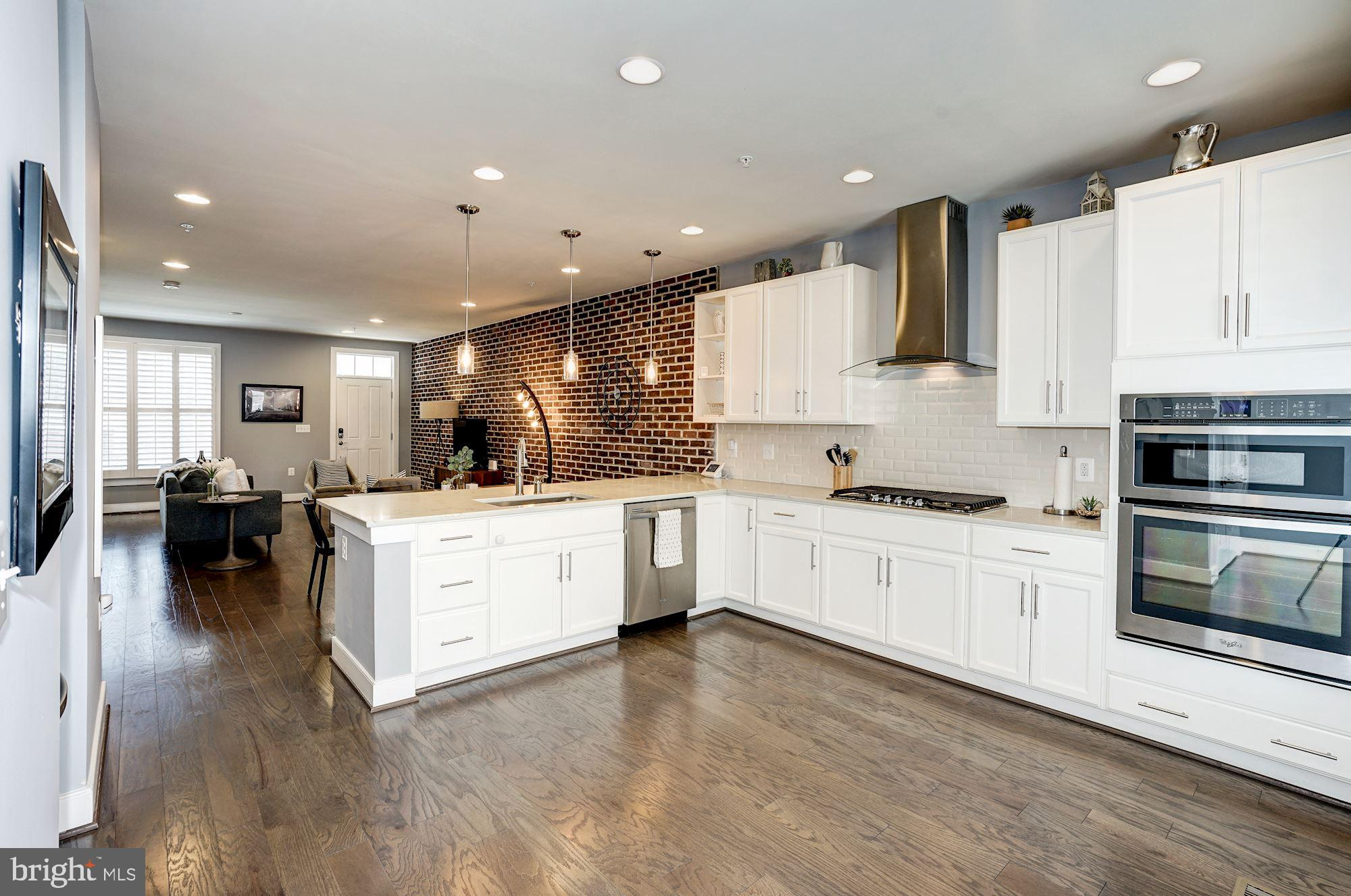 Rarely available in Potomac Yard! 4 level town house with a walk-out basement and a fenced back yard. Estimated 3700SF including basement. Entry into home on main level creates for a less vertical living.  Open floor plan. Main level has hardwood floors, recessed lighting, pendant lighting, plantation shutters. Large brick accent wall in living/dining  room. Kitchen with quartz counters, breakfast bar, SS appliances, back splash is open to a separate breakfast room. Breakfast room has a wall length pantry and opens onto a trex deck  with view of Masonic Temple. The upper level boasts of a master suite and a second bedroom with en-suite bath. Separate laundry room on this level has shelving and a retractable clothes line.  The spacious top level features a family room and office area with view of  Masonic Temple, in addition to a third bedroom with walk-in closet and a third bath plus utility closet.   Upper two levels have updated luxury vinyl plank flooring.  Lower level is a large walk-out basement waiting for your finishing touches... It is dry-walled and has rough-in for a bath. In addition it also has a large utility / storage room with windows and storage under the stairs. Great use as storage or finish off as as you please ..a possible media/game room, in-law/au-pair suite?  Basement opens onto a brick patio and a fenced-in back yard. This townhouse is within walking distance to Braddock metro. Amenities galore: playground, dog park, sports courts, playing fields, walking path. Near Del Ray main avenue w/ eateries and restaurants. Just south of Crystal City, future Amazon HQ2, near Old Town Alexandria, National Reagan airport, Pentagon. Mins to DC , National Harbor, Ft. Belvoir...