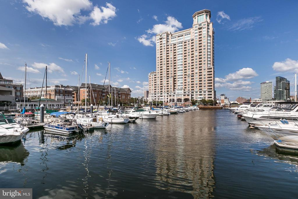 Exceptional luxury Harborview Towers opportunity!  NEW PAINT THRU-OUT. IMPRESSIVE BREATHTAKING VIEWS capture the Inner Harbor waterways and exciting city life!! Welcome to this luxury condo through a French double-door entry where quality interior of gleaming Brazilian Cherry hardwood flooring, custom gourmet kitchen with high gloss wood cabinetry, soft close drawers, solid surface counters, double sink, stainless GE Profile appliances, custom ornamental niche shelving, under counter lighting and breakfast bar with decorative pendant lighting. Spacious kitchen allows for spectacular prime window seating every day! This home offers a desirable floor plan with two private bedrooms, two full baths and 1,570sf. The Master Suite features a large bay window, balcony entrance, spacious walk-in closet with custom finishes. Master Bath bubble tub, shower tile accents, dual vessel bowl sinks, and bright accent lighting. Second bedroom features private balcony and custom book shelving. Comfortable luxury living and two balconies for all-year indoor and outdoor entertaining enjoyment! Harborview Towers offers an array of building amenities and services including 24/7 front desk concierge with garage valet, 24/7 extensive fitness center, in/out-door pools, steam/sauna, guest suites, social lounge, billiard room, dining and business rooms, bike storage, beautifully landscaped grounds, walking/jogging paths, on-site restaurant, gourmet deli, security staff, fountains, marina, garage and guest parking! Excellent location near downtown business district, MARC train, BWI International Airport, stadiums, nightlife and shopping! A MUST SEE!! OPEN HOUSE THIS WEEKEND!