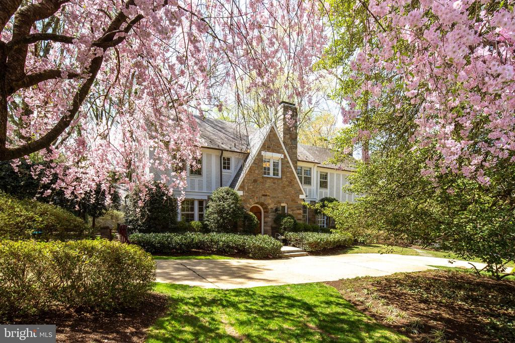 For the first time in 70 years, this elegant Tudor is available for sale on the open market.  Previous owners have included a Supreme Court Justice, U.S. Senator, and a Navy Admiral.  The main level provides 9' ceilings, a spacious dining room with alcove window, living room with fireplace, family room with fireplace and wet bar, den, powder room, kitchen, and a laundry room.  A large terrace is accessed through the den and family room. The upper level is configured to be either a master suite with his and her baths, a dressing room, and a sitting room plus two bedrooms with a shared bath.  The top floor offers a 5th bedroom with en-suite bath, and extra storage or room for expansion.  The lower level is semi-finished with an outside entrance, and a half bath.  The home is surrounded by beautiful gardens .