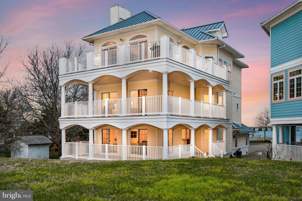 Enormous views without the enormous price! Located in the private neighborhood of Harbor Lights, once entering your friends and family will never want to see the OceanCity fireworks from anywhere but here. Enjoy the expansive views of downtown OceanCity, Ocean City Inlet and Assateague Island right from any one of the three wrap-around decks or head over to Homer Gudelsky Park where you can enjoy some great surf fishing to catch your dinner. This estate style home is also conveniently located near many great West OC restaurants, shopping, boating, and the beach. As you enter the home you are greeted by your In-law suite, Guest quarters, or MediaRoom, you Name It! This area has a bedroom, full bath, large living space with breakfast bar and mini kitchen, plus a wrap-around covered porch to enjoy the breeze of the ocean from the inlet, great for entertaining. This home includes an elevator for those who choose not to use the steps to the next level. This level includes the master suite with ample room for a sitting area to call your own. If you thought the first floor has beautiful views, well just imagine opening your eyes to the rising of the sun. What a wonderful way to ease into your day. Imagine cool nights relaxing with the comfort of your gas fireplace, a throw, and a good book. There is also a large walk-in closet with shelving and Center Island. Beautiful master bath with jetted whirlpool tub to relax in after a long day of sun and fun. Separate lavish shower, sprawling double sink with a step-down vanity to sit at while putting on the finishing touches. For your convenience located just outside of your Master Suite is your laundry room. Across the hall is another bedroom with its own en-suite bath and walk-in closet. Now let~s not forget the beautiful view of the beach, bay, bridge and Ocean City skyline. Last but not least the top floor has all the elegance and class you have been wanting. All the hardwood floors throughout the living area have just been refinished. The dining room has an expansive dining table for those formal dinner parties and holiday events. The living area with all of its beauty has a gas fireplace and custom built-in shelving and epic sliding glass doors surround the living room where the view is the artwork and the subject of many conversations. Watch endless sunrises and sunsets from this wraparound open-air deck. Sunbathing, grilling, bird watching, people watching or just relaxing - the options are too numerous to name. Now while you entertain you~ll be cooking in your state-of-the-art gourmet kitchen with spacious custom cabinets, center island, stainless steel appliances and still be part of the fun. Where will you store all your water and outdoor toys you ask - In your spacious 2-car garage, of course. This is Coastal Resort Living at its Finest! all for your private showing or come preview this beauty Thursday - Sat 10 am to 3 pm.  I promise you won't be sorry!