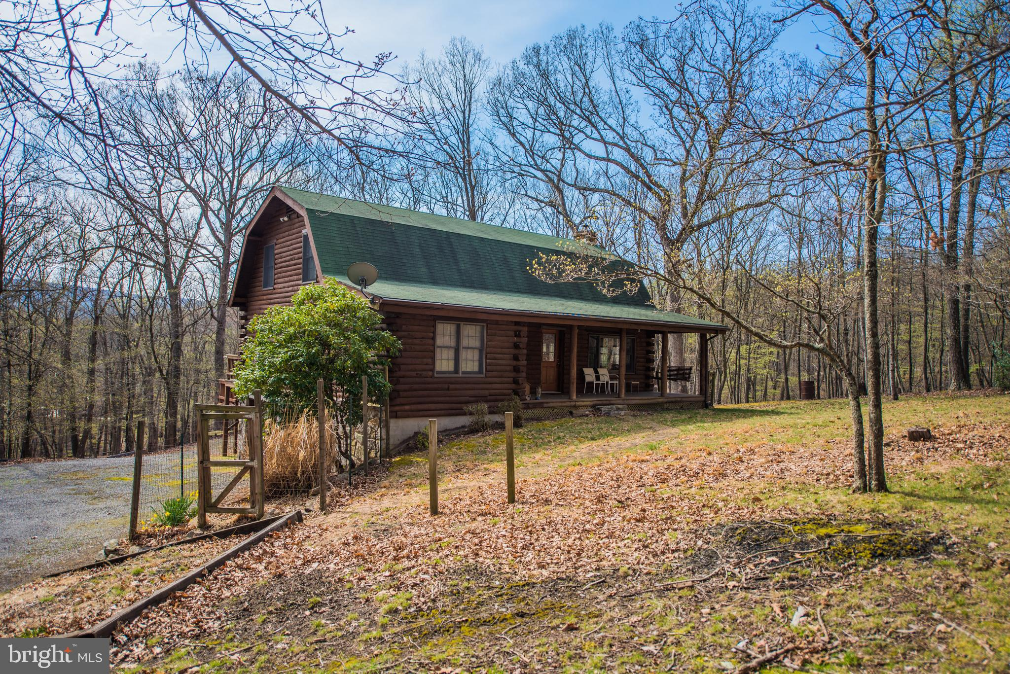 Nice 3 level log home on 4.8 mostly wooded acres with partially fenced yard. Enjoy sitting on the covered front porch or rear deck to watch the wildlife. Private river access on the Cacapon River for the community with picnic area with bath house and barbecue areas.  Three bedroom and two baths, lovely living room with woodstove, open dining kitchen area.  Basement has nice workshop area and two car garage.