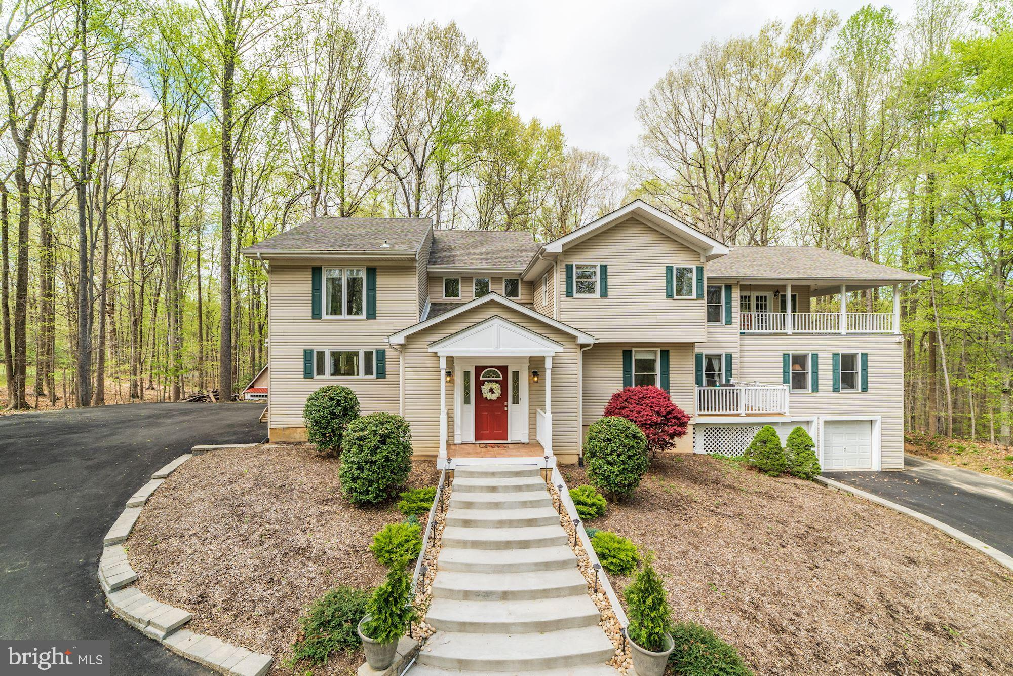 A piece of the country in the heart of the suburbs - Don't miss this GEM! Custom 6 BR, 6 BA home nestled among 2 acres of gorgeous wooded privacy. Open concept 1st floor living space includes cozy reading room w/ fireplace, remodeled kitchen w/ stainless steel appliances, granite counters, and hardwood bar counter. Library/office w/ private deck. 2 Master suites, perfect for in-law or au pair. Expansive owner suite w/ large separated sitting room, master bath w/ jacuzzi tub, his & her walk-in closets, and laundry room! Stunning views from the bedroom private 3-sided wrap-around porch! Property has freshly-paved wrap-around driveway, two sheds (1 w/ chicken coop), hardscape firepit, and countless mature hardwoods/evergreens. 3-car garage, separate indoor workshop, new roof, gutter-guards, & newer HVAC. This home is zoned for the county newest Elementary school opening August 2019. Conveniently located 10 minutes from Potomac Mills Mall and interstate 95. Endless custom features throughout (even a secret bookcase door!). A MUST SEE!