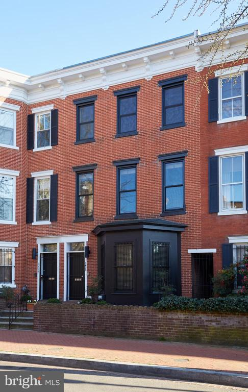 Open Saturday from 1-3 - A gem in the heart of Logan Circle. This fully renovated 3 bedroom, 3 full and one half bathroom townhome stretches out over three levels, with a flexible floor plan. A modern and stylish mix of space, finishes, and location, this 1880 Federal home boasts open and light-filled living spaces. The home is punctuated with beautiful details including stunning hardwoods, soaring ceilings, two wood-burning fireplaces, and custom built-ins. The living room is exceptional, completely sun-drenched with oversized windows and room to stretch out. This flows right to the Chef's kitchen, outfitted with top-of-the-line stainless steel appliances, including sub-zero refrigeration and a Bosch suite. An amazing bonus to the home is the screened in porch- creating an oasis in the middle of the city. The Owner's Suite is truly spectacular, adorned with vaulted ceilings, a fireplace, spa-like ensuite bathroom with a large double vanity, and a spacious walk-in closet. This home has the incredible opportunity to be converted back into a separately metered two-unit unit home. The possibilities are endless here- think rental potential, au pair suite, in-law suite, and more. Finally, the two car parking is what makes this opportunity one that cannot be missed. The vibrancy and convenience of this prized location speaks for itself. Near the METRO, a multitude of green spaces, and some of the city's most sought after shopping, dining, and socializing establishments, this premier Logan Circle residence is an exceptional place to call home.