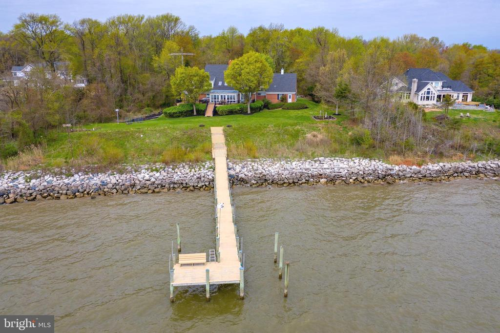 Classic elegance abounds in this 4124sf all brick custom home, built by Bert Winchester, and sited on private 4.12 acres in gated Bodkin Pointe. The property boasts 212' of rip rapped shoreline with southeast exposure on the Chesapeake Bay.  Spectacular panoramic water views from the 2 story great room, breakfast nook, and main level owners' suite. The sweeping 64' waterside mainteance free deck has multiple steps to the expansive front yard and 100' private pier with electic, water, and typical 4' depth. Enter from the covered portico into the two story foyer with marble flooring & circular stairway. The formal living room has a wood burning fireplace flanked by built in cabinetry & display shelving. The focal point of adjacent formal dining room is the exquisite imported Waterford crystal chandelier. Sunshine and bay breezes flood the 2 story great room featuring 2 story stone fireplace, skylights, and soaring vaulted ceiling,  Main level owners' suite has bedroom with sliding doors to the deck, private study, and  beautifully remodeled bath with custom marble flooring, walls, and walk in shower. Upper level consists of 3 bedrooms, 2 full baths, and separate unfinished bonus room with cedar closet. Unfinished lower level with rough in and walkout to yard has endless possibilities. Bodkin Pointe has community tennis, beach, and marina with deep water slips available.