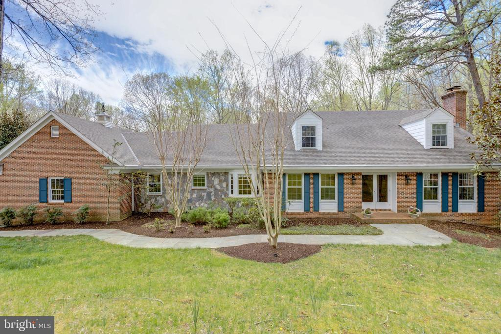 Price improvement and Open Sunday June 23, 2019 1-4 p.m. Welcome to the warmth and charm of 10415 Dominion Valley Drive~If you are looking for a retreat from Northern Virginia madness, you have found it on Dominion Valley Drive. This beautiful classic home on 5 acres has a stunning sunroom with vaulted ceiling and a view of the tennis court. The family room, living room and recreation room entice you to relax in front of the 3 cozy fireplaces, while the inviting country kitchen with granite counters, stainless steel appliances and a 6-burner gas stove creates a space for pleasant gathering. The washer and dryer are off the kitchen in their own quiet nook. Two bright and cheerful bedrooms with a full bath create a wonderful in-law suite on the main level and a second similar two-bedroom suite, perhaps for an au-pair, can be found on the lower level. The basement also includes a spacious recreation room with a wet bar or kitchenette;  a roomy office with built in desk and cabinets; as well as oodles of finished storage including a large cedar closet; a workroom for messy projects and a second full size washer with hook up for a dryer; there are outside entrances on the lower level from both the recreation room and office to the back of the house. The master bath has been renovated to include double sinks and a large shower stall. The two upper levels are all hardwood floors except for the sunroom which has beautiful slate flooring. The two-car garage is oversize with high ceilings, built-in shelving and space to park a boat. Every generation will find something to love in this exceptional property.Leave the hustle and bustle, but know everything you need is only a few short minutes down the road~The peaceful Shadowalk community is nestled between Lorton and Burke in the Fountainhead district of Fairfax Station. The neighborhood is extremely horse friendly with its own beautifully maintained trails.Only 5 minutes away, Fountainhead Park has more horse trails with bikin
