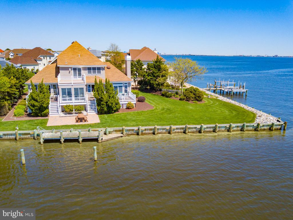 Best Waterfront location in Ocean Pines with boat dock and great access to open water. This home is situated on a beautifully landscaped lot, with southern exposure in the rear of the home.  You will enjoy unobstructed panoramic water views & gorgeous sunrises. There is plenty of outdoor living from the 4 waterfront decks, covered front porch and large yard.Owned by long time owner. Home features a sunroom, elegant family room with floor to ceiling windows to take advantage of the natural sunlight and water views. This home offers 3 bedrooms, all featuring a private bathroom. The first floor master suite includes a large bathroom, walk in closet and access a rear deck.  There is also a den/office on the 1st floor that could easily be converted into a 4th bedroom.  The kitchen features white cabinetry,  solid surface counters and a counter bar. The roof was replaced in 2007, and the 1st floor gas furnace was replaced in 2013.  Need storage         space? There is a 2 car garage, floored attic with pull down stairs and a walk in storage area. 1 year home warranty to buyer. Enjoy all the community of Ocean Pines has to offer including Yacht Club and restaurant, 5 swimming pools (1 enclosed), Robert Trent Jones golf course, marina, Community Center, Beach Club on the ocean, community police and fire departments, skate park, dog park, playgrounds, racket               complex with 8 pickle ball courts.