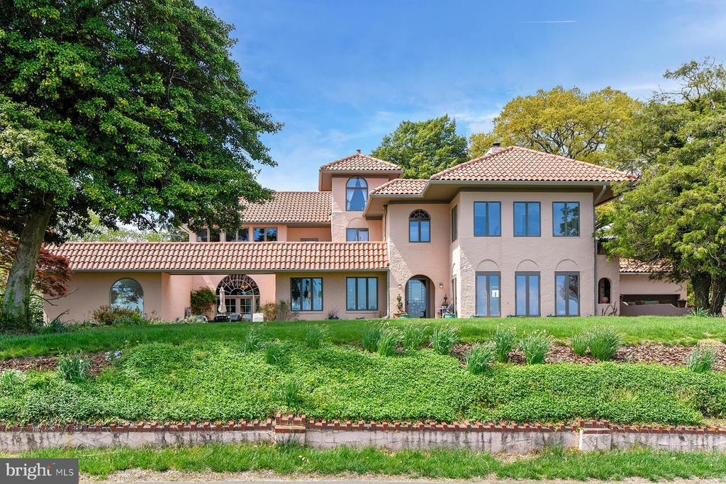 The most iconic home in Bay Ridge has not been offered for sale in more than 40 years! 31 Bay Drive is a Mediterranean style home with absolutely incredible Chesapeake Bay views and an indoor, fully-tiled pool.  This 5-bedroom, 5 bathroom home is situated on a pristine lot, totaling almost half an acre, with lush mature landscaping.  The water privileged community of Bay Ridge, once known as The Queen Resort of the Chesapeake, offers many amenities. The Bay Ridge marina located on protected Lake Ogleton has deep water slips, and an adjoining playground. 31 Bay Drive owners are charter members of the community pool; the membership transfers with the home. There is also access to common areas including the beaches and park and there~s even a summer camp! As a highly sought-after community in Annapolis with so much to offer, including a convenient location, the community of Bay Ridge makes this magnificent home that much more special. As you step into the 1924 home you are immediately greeted by the stunning character and charm that is carried throughout.  The living room has an exposed wood-beamed ceiling, a brick-surround wood-burning fireplace, and a wall of windows to take in the exceptional water views. There are three solid mahogany pocket doors that are said to have come from the old Hay Adams home in Washington DC. The staircase is also original to the home and highlights the craftsmanship of an earlier era. Through the living room to the left is a stunning library with custom wood paneling, built-in bookshelves, and a wood-burning fireplace. Step out of the library to the water view patio: it is the perfect spot to have total privacy while enjoying the panoramic views. To the right of the living room is the formal dining room with the same exposed wood-beams and a gorgeous gas fireplace.  This room is also situated strategically on the land to get optimal views of the Bay. Through the dining room is the gorgeously updated kitchen with marble countertops, center island, beautiful cabinetry, and updated appliances.  The kitchen opens to a large family room with a sitting area, full bar, and access to the attached two-car garage.  Upstairs, the luxurious master bedroom suite enjoys sweeping Bay views and has a private en-suite bath with a large soaking tub, separate shower, stackable laundry, a coffee bar, and access to a private balcony overlooking the Bay.  This space truly offers a peaceful retreat from the day. There are two additional bedrooms on this level that share a hall bathroom.  Up just a few stairs, a portion of the attic has been finished and makes for a perfect reading nook with huge water views; there~s an adjoining full bathroom. The separate in-law apartment suite on the second floor has a second kitchen, a living room, a sunroom, and two bedrooms that share a full bathroom.  The apartment has its own outdoor space, which overlooks the Bay. It is all here -- the elegance of a bygone era that has been updated to include geo-thermal heat and new 150 year roof. Ten years ago, the owners built the library, pool, and garage additions to make this a truly spectacular oasis.