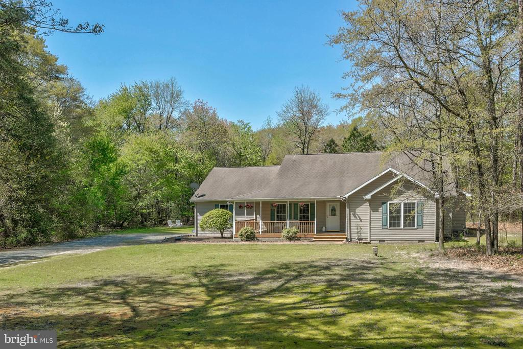 Bright cheerful rancher with a popular floorplan that~s functional and gorgeous located on a spacious 2.37+ acre lot 20mi to Ocean City; 12mi to Salisbury. A welcoming front porch overlooks the expansive yard in a serene setting. An inviting open concept floor plan with a sweeping living room featuring beautiful wood floors, vaulted ceilings, spacious eat-in kitchen that boasting oversized counter seating, and tile floors. The home features a formal dining room which could also function as an office, full-size laundry room, and 2nd-floor oversized finished attic or bonus room. A main-floor master bedroom includes custom wood shelving in the walk-in closet, ensuite full bath with double vanity, jacuzzi tub, and shower. Entertaining rear deck overlooks the scenic yard backing to trees. The attached 2 car garage has an enlarged workbench area. Extras include an alarm security camera system, crawl space dehumidifier, and a one-year home warranty.