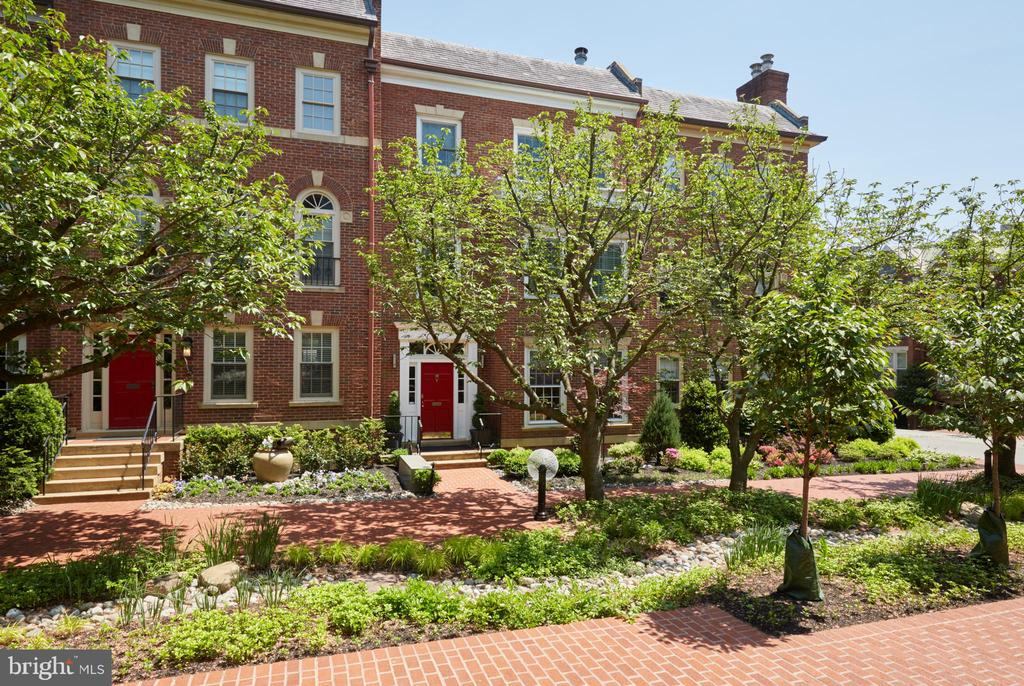 This Georgetown home is the largest size rowhouse in the original Cloisters community. It is meticulously and completely updated with four levels and an Elevator. The charming brick facade is well-situated and protected from the city as it opens onto a large and spectacular courtyard, Cherry Court, with well-manicured landscaping and cherry trees maintained by the community's very affordable and friendly community and HOA, which also manages snow removal to the front door. The private garden in front and gated patio in the rear of the home allows the owner to create an enchanting and personal retreat too. The beautifully appointed and fully renovated kitchen includes Murano Venetian glass pendant lights and an exquisite and unique LED chandelier. The area connects to a large living room with very good flow for entertaining and family gatherings. Most floors are hardwood and the stairwells have durable feature carpet with leather trim and a matching dark hardwood handrail for an elegant and lasting style. The master level is completely renovated and re-designed and includes several exquisite features, including an architect created and visually spectacular curved wall in the master suite. There is also a well-appointed and stunning master bath with heated floors and a stand-alone feature tub contained inside the large shower suite. The master closet is a virtual retreat in itself with luxury handmade cabinets and a beverage fridge and bar area for refreshments too. On the third level, there are three bedrooms, one with an attached bath, and all full bathrooms in the home have European style heated towel racks installed as well as power flush toilets. The basement features a full bedroom and bathroom, with heated floor, as well as a large den that has a luxury tempurpedic murphy style bed for guests and can also be used as an entertainment oasis with a beverage fridge and bar sink too. Laundry and generous storage are found on the top and basement levels for the ultimate in convenience and most of the house systems, including HVAC and the roof, are brand new. The house features keypad locks, including on the backyard gate, sunrise and sunset timers on the front porch and rear lights and has two parking spaces with motion-sensor lights in the rear of the home as well as a trash and recycling storage enclosure that can be used for other gear as well. There is a wall-mounted fountain in the back garden which helps create a splendid nature retreat. The house has been exquisitely renovated and maintained and awaits its next loving owner.