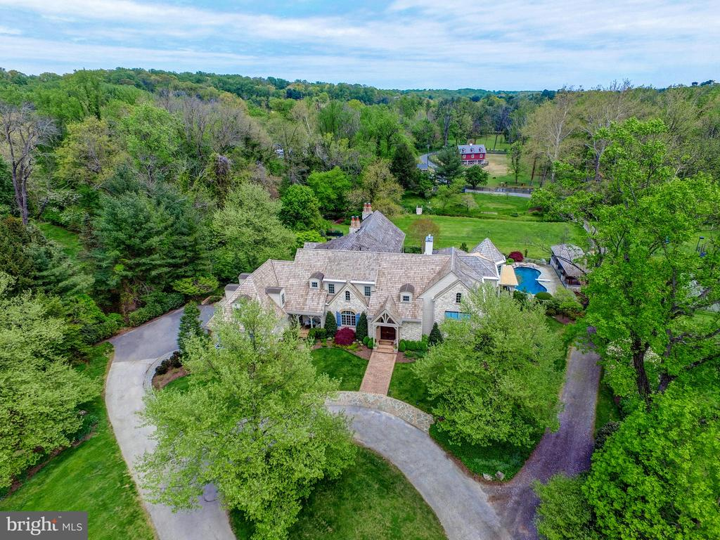 SUBSTANTIAL PRICE REDUCTION! STUNNING FRENCH COUNTRY ESTATE ON OVER 15 MAGNIFICENT ACRES IN THE HEART OF THE GREENSPRING VALLEY. TRULY A UNIQUE OFFERING TO HAVE THE ALLURE OF COUNTRY LIVING WITH CLOSE PROXIMITY TO THE CONVENIENCES OF THE CITY. THE EXQUISITE FORMAL SPACES COMBINED WITH THE CASUAL LIVING SPACES INTEGRATE TO MAKE THE BEST OF BOTH WORLDS IN THIS SPECIAL PROPERTY, TWO STORY FOYER LEADS INTO THE STUNNING LIVING ROOM, BILLIARDS ROOM AND OFFICE, 1ST FLOOR BEDROOM AND BATH, OPEN DINING ROOM, CUSTOM GOURMET CHEF'S KITCHEN WITH SUN FILLED BREAKFAST AREA AND CATHEDRAL BEAMED FAMILY ROOM. BRICK FLOORED MUDROOM AND UTILITY ROOM. THE ADDITION OF A FLAWLESS WOOD PANELED LIBRARY AND SITTING AREA ARE BLENDED TO PERFECTION. GORGEOUS MASTER SUITE AND SITTING ROOM PLUS SIX OTHER BEDROOMS AND ADDITIONAL BATHS WITH MANY DIFFERENT OPTIONS FOR FLEXIBILITY AND LIFESTYLE CHOICES. RECREATION ROOM, GYM, WINE ROOM/BAR AND INDOOR LAP POOL ARE OFFERED IN LOWER LEVEL FOR RECREATION. THIS PROPERTY ALSO OFFERS MANY EXTERIOR AMENITIES WORTH MENTIONING FROM THE BREATH TAKING BALCONIES OVERLOOKING THE GROUNDS, SWIMMING POOL AND CABANA, SCREENED PORCHES, CUSTOM BARN, PADDOCK, TREEHOUSE, CHICKEN COOP, TENNIS COURT, STREAM, POND, VEGETABLE GARDEN AND MANICURED LAWNS AND TRAILS THROUGH THE WOODS JUST TO MENTION A FEW. PRIVATE DRIVE AND THREE CAR ATTACHED GARAGE.  A TRUE PLEASURE TO EXPERIENCE!