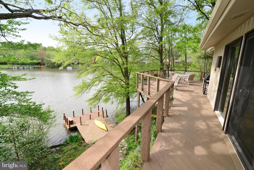 Welcome to this beautiful waterfront home on Lake Audubon!  Get ready to watch some great sunsets and enjoy waterfront living!  This home offers a spacious, flexible floor plan, great natural light and waterfront views!  The entire interior is freshly painted. There are four bedrooms and three and one-half bathrooms. The fourth bedroom on the lower level is currently used as an office. The main level has a large family room and living room - both with vaulted ceilings, skylights, recessed lights, and sliding glass doors which lead to the main level deck with lake views.  There is a three-sided gas fireplace with a raised stone hearth and stone accent wall in between the family room and living room. The fireplace also features custom glass doors and a custom metal mantel.  The dining room overlooks the living room.  The kitchen features a breakfast room with skylights and a wall of windows.  The kitchen also has granite counters, a center island, great cabinet space, recessed lighting, under-cabinet lighting and stainless steel appliances.  The kitchen overlooks the family room and living room.  The layout is great for entertaining with an open design, spacious rooms and high ceilings.  There is also a main level office with built-in desk space and shelving, and there is a french door leading to the side lawn and a stone walkway.  The owner's suite has a vaulted ceiling, large windows, a gas fireplace, built-in bookcases and a large, walk-in closet.  The owner's suite bathroom has a glass-enclosed shower, separate tub, separate water closet, a vaulted ceiling, skylights and ceramic tile. Up one level from the owner's suite are Bedrooms #2 and #3, both offering lake views! There is also a full bathroom with a window also offering lake views on this level! There is also a walk-in attic, a double-door linen closet and a walk-in cedar closet on this level.  The lower level bedroom has new flooring, a wall of Andersen windows offering lake views, and a Pella sliding glass door leading to the lower level deck, stone walkway and the private dock. There is also a full bathroom on this level, as well as an unfinished room, which could be finished or simply used as storage space.  This room has a window with waterfront views, so it could be a perfect workout room or other finished space. The outdoor space is awesome, with a main level deck with stairs to the lower level deck and stone steps to the private dock. The dock and the decks are composite for easy maintenance.  The home also has beautiful landscaping and hardscaping.  Located on a quiet cul-de-sac with great waterfront views, the location is great:  close to the Wiehle Ave. Silver Line Metro, shopping and restaurants, but also just steps away from Reston's great trails, pools and tennis courts.
