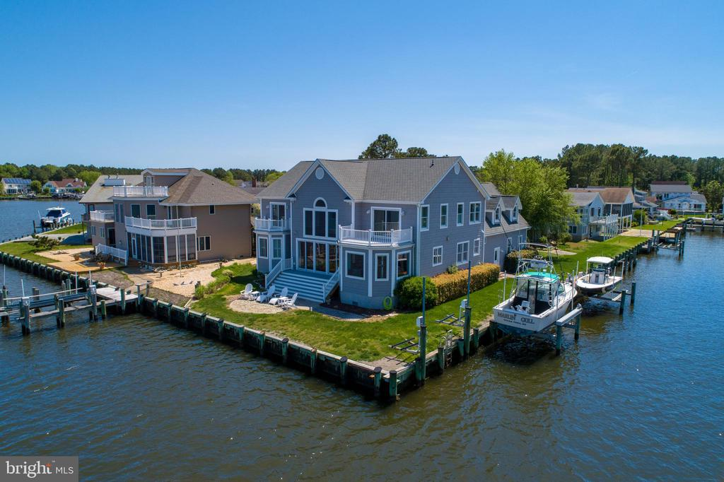 Magnificent custom direct waterfront home 6BR/6.5BA boasting 5000 sq. ft. with 150 feet of bulk headed waterfront hits the market! True perfection can be found throughout this home.  Imagine how good it would feel to relax in your home on the open water with the Ocean City skyline as your backdrop.  If you are looking for the ultimate waterfront property that also accommodates all your boating needs look no further.  This home has two boat lifts, one 16,000lb and the other 8,000lb, and 2 Jet Ski lifts.  As you walk through the front door you will be immediately drawn to the breathtaking water views.  You will love the open floor plan, hardwood floors, custom built ins and the soaring cathedral ceilings.  The professional chefs kitchen has a large center island, stainless steel appliances and tile backsplash, custom cabinets, walk in pantry and a breakfast area overlooking the water. The dining room is off the kitchen also with water views. The great room has a wall of windows and sliders making this home light and airy.  Off the great room is a deck leading to a patio overlooking the water for relaxing with friends and family. There is a double sided gas fireplace for ultimate all season luxury living. The downstairs master is fabulous, has its own fireplace, and overlooks the water creating the perfect setting to unwind. The lavish master bath is sure to delight you with a jacuzzi tub, rain shower and double vanities.  Completing the master is an oversized walk-in master closet and a separate sitting room.  The sitting room has its own entry and could also be used as a first floor office or 7th bedroom.  Finishing off the first floor is another full bath, laundry and mud room.  The oversized garage will sure to please the car enthusiast with high ceilings and extended length and height for large trucks and SUV's.  Off the mud room there is a separate private entrance that takes you upstairs to the inviting guest quarters that also could be used as a second family room or game room.  It is 24' x 35' with hardwood flooring and wet bar.  There is an upgraded full bath off the guest quarters. You will love the separate office workspace perfect for a quiet place to work.   There are 4 additional large bedrooms on the second floor and 2 of those bedrooms have waterfront balconies to enjoy morning coffee. There is also a loft area to sit and relax overlooking the water.  This home is in a premier location. You will love taking the boat to one of the many restaurants and bars, or simply enjoy a night on the water.  Whether its jet skiing, boating, kayaking, paddle boarding, fishing or crabbing it can all be done right from your waterfront dream home located at 4 Clubhouse Drive in Ocean Pines!   This home was designed  as the builder's custom home- - Mill Creek Builders and can accommodate 8 cars for parking in the driveway. Call today for your personal tour and live the lifestyle you always dreamed about and watch mesmerizing sunrises.