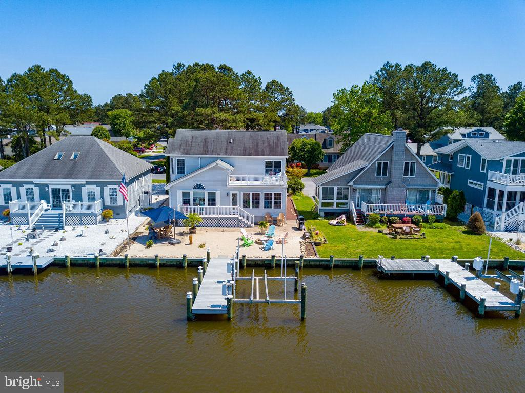 Imagine walking into a Luxurious Waterfront Coastal Style Custom built home with Direct Access to the Bay including newer dock, bulkhead, 10 lb boatlift, personal beach oasis and dock can accommodate your jet skiis l!! This 3 bedroom 2.5 baths home boasts soaring cathedral ceilings, skylights, mantel gas fireplace in Living Room, stunning hardwood floors throughout the first level and soft Caribbean Designer paint colors through out this impressive home. The Chef of the family will appreciate Custom designed gourmet kitchen with hand crafted kitchen cabinetry etched crab glass door inserts, custom granite counter tops, tile backsplash complete with Samsung 4 French Doors Stainless Refrigerator, Samsung 30 inch Stainless slide in electric Range with Flex Duo Over, Samsung Stainless Storm 6 wash cycles  dishwasher, Edge Star Built in Dual Wine Cooler and designer light fixtures. . Enjoy your morning coffee in sitting room, sun room or on your private beach overlooking the serene waterfront view.  . Retire to your well-appointed master suite with private waterfront balcony enjoying the evening sunsets. Plenty of room for family and friends to visit  in oversized bedrooms with lots of storage and closet space.  Home is complete with Attached Garage, New Kenmore Washer and Dryer, New Lennox Elite series Heat pump , Comfort Wi Fi thermostat, Elite Series Gas furnace installed in 2017  Custom. This Exquisite home will not last long truly a must see!