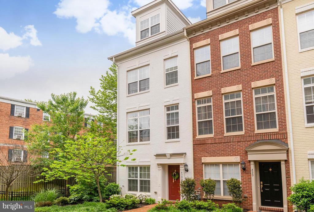 Fabulous four-level, end-unit brick townhome tucked away in a courtyard, yet right in the middle of all the Ballston excitement!!!  Extra windows with southwest exposure make this home simply delightful!!!  Hardwood floors on living/kitchen and master bedroom levels.   Gorgeous wood staircases with runners.  Large open kitchen with granite island and bar stool seating.   Top-of-the-line tall cabinetry with pull-out shelves.  Living room / family room right off kitchen.  Large dining room with designer lighting and tall palladium windows.  Master suite with two walk-in closets and luxury bath.  Separate tub and shower and granite counter!!!  Second bedroom filled with windows, walk-in closet and second full bath.  Uppermost level has awesome third bedroom with en suite full bath.  Large enough for a desk/office area!!  Wonderful roof-top balcony overlooking trees.  Dedicated natural gas connection for a grill.  Two-car garage with tandem parking.  Walk to all the new Ballston shops and Metro.  This home has been loved and shines!!!