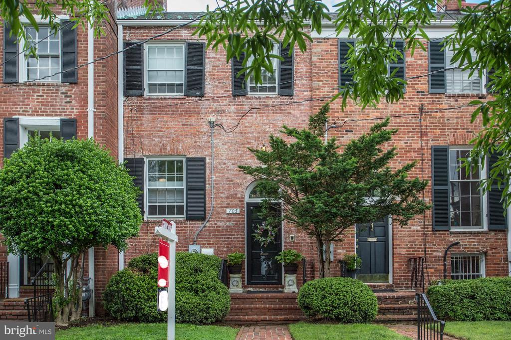 Completely renovated, 3-level, brick townhome located in the Yates Gardens neighborhood of the Southeast Quadrant of Old Town Alexandria! Walls were removed and reconfigured to create new, open floor plans on the First and Third levels of the home. The First Floor comprises heated floors throughout, an open kitchen with a spacious island with granite countertops, a copper forged bar sink, additional storage and seating for four.   The space is complemented by a separate dining area which leads to the outdoor, private oasis - a large brick patio and tiered garden of mature plantings and trees.The Second Floor living room is light-filled and open with floor-to-ceiling windows, a wood-burning fireplace, and a reading cove bookended with built-ins. The Third Floor comprises a master bedroom with en suite bath, and a double-sided, walk-in closet. The owner added a second full bath to complement the guest bedroom. The attic space has been transformed into an accessible space with pull-down steps and sub-flooring to provide off-season storage. There is one assigned off-street parking space located at the foot of the front door. This home has it all!