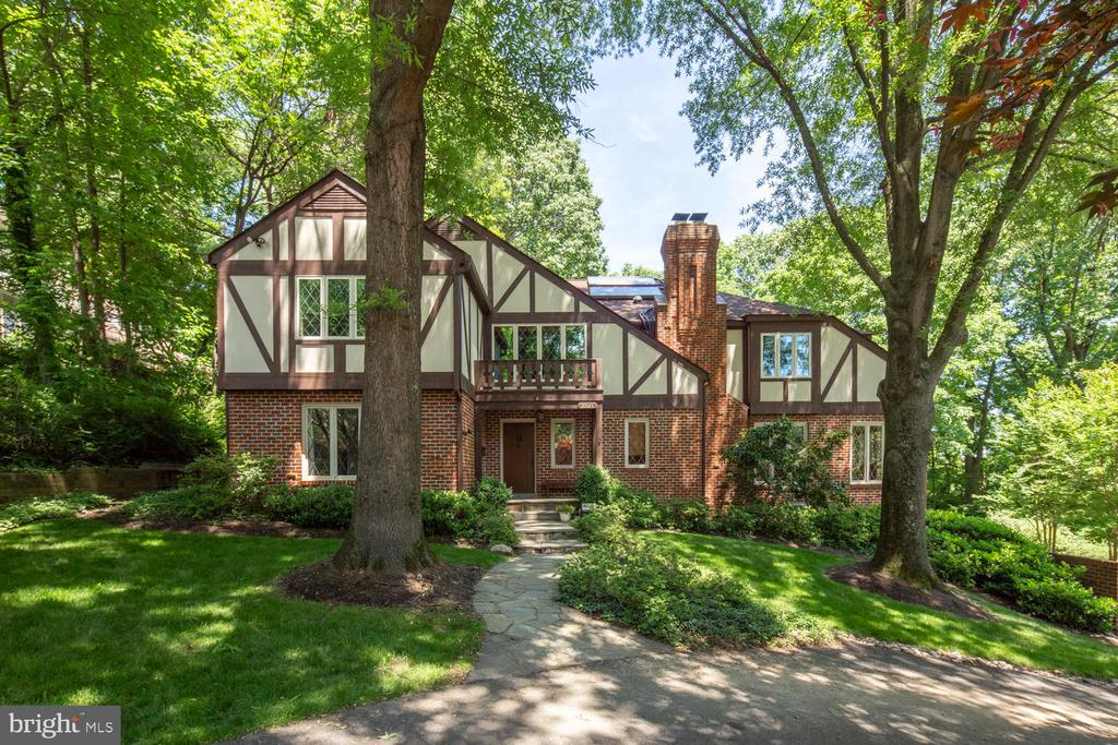 Traditional Tudor, on a non-thru street, is the ideal backdrop for the story of your life! This charming storybook 1/2 acre property is positioned only a property away from Potomac Overlook Regional Park for hiking adventures. Adventures are made easier with a low-maintenance exterior of brick and Hardi for durability and minimal upkeep. Upon entry, one is greeted by a 2-story entry foyer with classic Tudor architectural details. The main level boasts substantial entertaining spaces with a wonderful flow. The residence's provides a living room accommodating multiple seating areas; a spacious dining room for large family gatherings and formal entertaining; and a Chef's kitchen (SubZero, Electrolux induction cooktop with 2 ovens, island, granite and custom cherry cabinetry). Windows abound on this level. The main level continues by offering table space in the kitchen opening to 1,000 sq ft multi-tiered deck; a great room with soaring ceilings, wet bar, and wood-burning fireplace; a bedroom suite with en-suite bath; a hall half bath for guests; laundry and storage spaces; and a den overlooking the tranquil yard.  Four lovely bedrooms reside on the upper level - two sharing a Jack-and-Jill bath, but each providing its own vanity. A third bedroom is paired with a full hall bath. The owner's suite offers a seating area, a third wood-burning fireplace, dressing room, walk-in closet, and a master bath filled with light due beautiful skylights. The lower level of the home gives access to the 3-car side-load garage; storage spaces; wine cellar; and recreation room... and then there are the outdoor living spaces, to include an over-sized, multi-tiered deck, patio with fire pit, and ample lawn. There's a 6-zone sprinkler system for ease in caring for the gorgeous plantings. New roof (2014). Circular driveway. All only 2 traffic lights to Washington, DC.