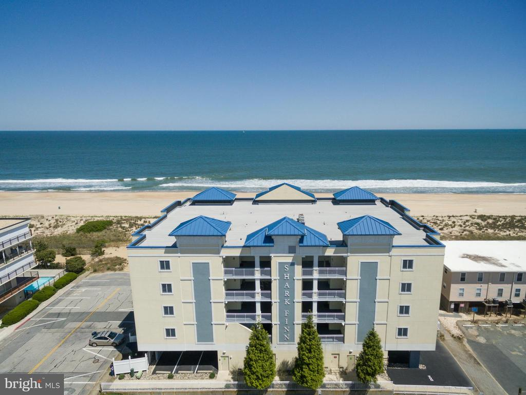 The Shark Finn oceanfront condominium is the most impressive luxury low-rise boutique condo building on the beach! Enjoy unobstructed oceanfront views and abundant natural light in this top 4th floor southeast corner end unit located on 125th in North Ocean City, Maryland. This is a rare opportunity to purchase almost 3,000 sq. feet, 4 bedrooms and 3 1/2 bathrooms as condos of this caliber rarely come on the market. Featuring an oceanfront master bedroom, wrap around balcony for outdoor entertaining, open concept floor plan, custom cabinetry, granite countertops, wet bar, gas fireplace and ceramic tile flooring. Fully furnished turnkey move in ready with excellent rental income potential. This unit has never been rented and is seldom used.