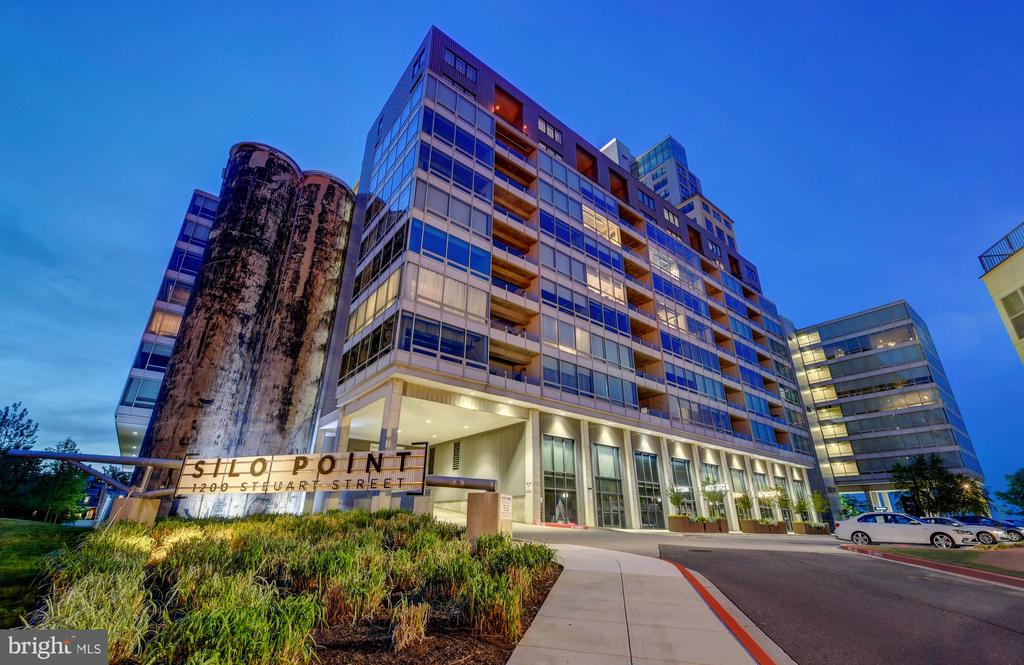 """*DRASTIC NEW PRICE* & **SELLER TO PAY $20,000 TOWARD  CLOSING COSTS**& ***SELLER TO PAY CONDO FEES FOR 1 YEAR!!***   BEST VALUE IN SILO POINT--- Its all about the views and soaring ceilings from this spectacular 15th floor condo in the  The  Industrial Modern """"Silo Point"""".  When you open the Lutron motorized shades, you will enjoy the ships and boats sailing by as the travel in and out of the Inner Harbor or watch the city light up as the sun goes down from the spacious balcony.  This 2 bedroom 2 and a half bath home is meticulously maintained and has a completely renovated chefs kitchen with induction cooking, upgraded stainless appliance and custom tile back splash.  Its gleaming, wide plank,  hardwoods are a perfect contrast to the soaring exposed original concrete columns from """"1923"""" only available in a rare few condos in the building.  The master suite features huge windows, soaring ceilings and a Lux master bath with soaking tub, double vanity and a separate shower.   The second bedroom is  for a den/office/ guest suite with full bath.  The foyer has additional storage and a full size stacked washer and dryer.  There are amazing water views from every room!  This home has two covered  premium deeded parking spaces as well.  Silo Point boasts a 19th floor Sky Lounge for entertaining as well as a full state of the art Fitness Center equipped with a Yoga and Pilates Studio and Message Therapy Rooms.  There is an additional space to entertain in the billiards and game room.  Just reserve the space with the 24 hour front desk staff.  Locust Point has wonderful access to I-95, is walking distance to the Water Taxi, a dog waking park, tennis & basketball courts and is a short drive to BWI.  One of the best neighborhoods in Baltimore City!  You will love living here."""