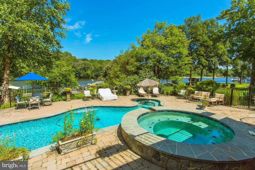 Deep waterfront custom home in Occoquan. If you have ever dreamed of vacationing at home, you do not want to miss this. Enjoy the cool summer breeze on your expansive deck overlooking the pool, hot tub and the gorgeous occoquan river. Have your friends come visit by boat where they can pull up to one of your many boat slips and enjoy a cold drink at the tiki bar. Complete with electricity and running water. Drop a line in to catch one of your favorite fish. Go paddle boarding on the river or take a casual stroll into town where you can dine, shop, or check out a museum! If you want some excitement, you are just a short boat ride from National Harbor or MGM. Some of the amazing custom features this home has to odder are: 2 story study with upper library, complete with 300 gallon fish tank, hidden door, fireplace and it's powder room. The main level master has a beautiful step down sitting area with fireplace, perfect for enjoying the gorgeous views, reading a book, or taking in a beautiful sunrise. Custom kitchen with Viking, open floor plan, enormous closets, boating, hiking, water sports... It's ALL outside your door!