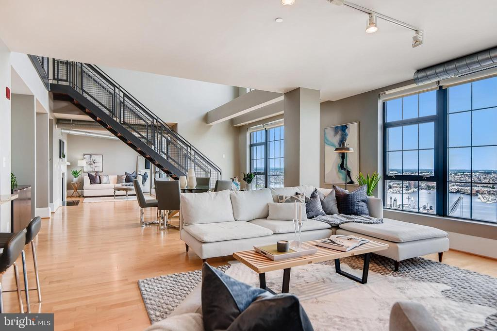 Extraordinary and rarely available duplex penthouse high on the 21st floor of Silo Point. Boasting over 2,600 square feet, this stunning 2-story, 2 bedroom with den and loft spaces, 2.5 bath has postcard views of the Patapsco River and Baltimore's Harbor from nearly every room. The foyer opens into a dramatic double height great room where soaring ceilings and walls of glass offer exceptional light and air and open city views, creating the ideal environment for entertaining and luxurious daily living alike. The first floor offers a cozy den with gas fireplace and access to the private balcony, storage room and a gourmet kitchen with oversized eat-in island, custom tile backsplash, gas cooktop and built-in wine refrigeration. A floating staircase draws you upstairs to a spacious loft area with eastern and western exposures. Retreat to the master bedroom suite featuring panoramic water views, a generous walk-in custom closet and a luxurious en-suite master bath with dual vanity, a walk-in shower, Kohler fixtures and separate soaking tub.  2 garage parking spaces convey with this offering. Live the Silo Point Sky life with full-service amenities; including 24-hour concierge, premier building manager, fitness center with adjoining yoga studio and private treatment room, boardroom, game room and 19th Floor Sky Lounge.