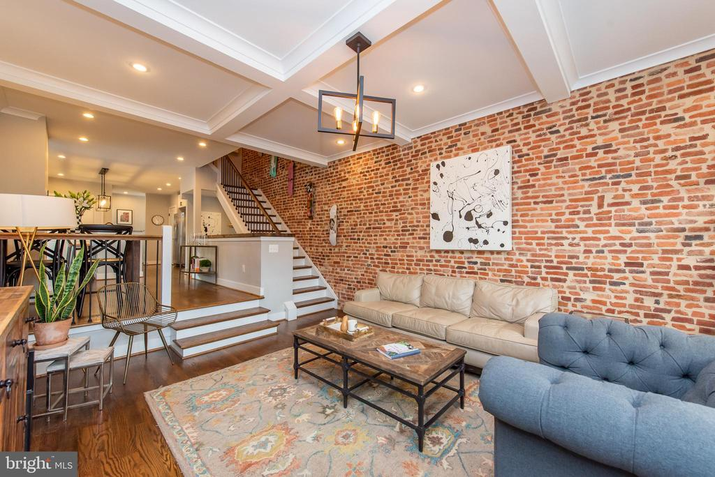 Potential 3rd bedroom suite - Extra wide, impeccably maintained corner row home in the heart of Hampden - steps from The Avenue - offers stylish finishes and expansive, light filled living spaces throughout!  Gorgeous wide plank hardwoods span the main level including spacious living room with exposed brick, coffered ceiling and bright store front style window leading to dining area and spectacular eat-in kitchen boasting granite counters, island with breakfast bar, on-trend light fixtures, stainless steel appliances and range hood, modern cabinetry and access to sizable deck.  Upper level hosts two serene suites with plush carpet, roomy walk in closets and custom shades and window treatments,   owner~s suite features 11 ft ceiling and luxe bathroom with an oversized walk in, dual head rain shower and stylish vanity. Both master Bedrooms have attached full baths on upper level.  Fully finished lower level features a cozy family room, full bathroom, flex space ideal for 3rd  master bedroom, home office or recreation with walk out access to more secluded patio and parking pad, and endless storage space including deep closet with additional washer and dryer hookup.  This home was custom rebuilt in 2017 and includes energy efficient appliances, smart lock and thermostat and many more thoughtful features while preserving plenty of original architectural details.  Prime, walkable Hampden location! Home Warranty Included! Open House Saturday 7/13 & Sunday 7/14 from 1-3pm.
