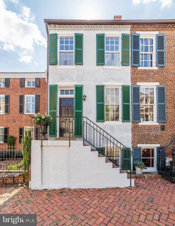 Sparkling brick 2 BR, 1.5 bath townhouse in prime location!  Double parlor living rooms, original hardwood floors, 2 wood burning fireplaces, deck off living room.  Dining room opens to patio and deep garden with tall mature trees and flowers.  Brick floor in kitchen and dining room with wainscoting.  Fireplaces covey as is.  This house is absolutely charming! Seller will pay 1 year of garage parking for 1 car in nearby Old Town commercial garage.