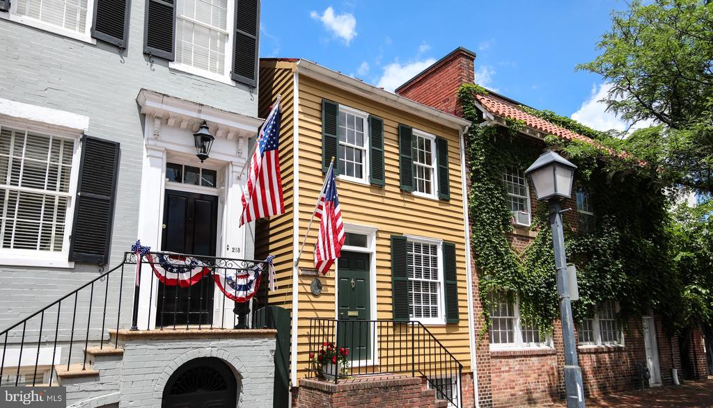 Located just a block and a half to King Street's shopping and dining district, this historic 3 bed, 2 1/2 bath clapboard row house abounds with charm and style. When you enter this delightful home from its brick stoop, you're greeted by a generous foyer with a spacious closet, a rarity in Old Town. Built circa 1800, the home has been extensively renovated for modern living, and features a thoughtfully designed kitchen to maximize storage, which is outfitted with Corian counters, an Italian tile backsplash, stainless steel appliances, and custom cherry cabinets. An open living and dining area complete with a wood burning fireplace, plantation shutters, crown molding, and hardwood floors features two glass doors providing easy access to the home~s private garden with flagstone patio, just perfect for al fresco dining, relaxing, and entertaining. Also located on this level is an updated, discreetly located powder room, and a staircase to the unfinished basement, which provides ample storage to suit your needs. Walking up the staircase you'll find two of the home's bright bedrooms and a large full bath on the second floor. As you enter the front bedroom, your eye is drawn upward by the exposed wood beams accentuating the vaulted ceilings. In the back of the home you'll find a quiet, serene second bedroom featuring the home~s second wood-burning fireplace, which overlooks the tranquil garden. Ascending the staircase to the third floor takes you to the home's master level complete with a spacious bedroom with sizeable closets, and a separate full bathroom with a soaking tub. A niche at the top of the stairs can make a charming reading or home office nook, and the washer and dryer are conveniently located near the bedrooms in a separate laundry space.The home's central location in the heart of Old Town's historic district is convenient to Whole Foods, Harris Teeter, Trader Joes, Starbucks, farmers' markets and the King Street Metro station, with easy access to I-95/495, Ro