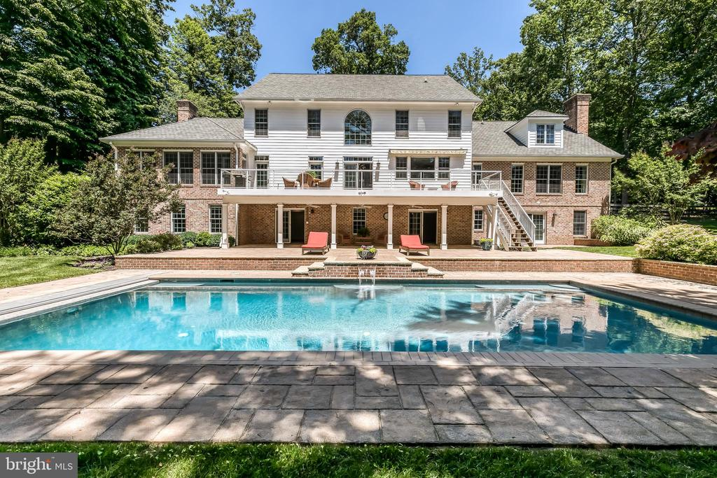 """Gracious custom built colonial with """"wow"""" and fine finishes plus contemporary proportions is situated on nearly three private acres in gated community bordering the Greenspring Valley. 6 Bedrooms, 5 Full Baths, 1 Half Bath plus a multitude of indoor and outdoor entertaining spaces. Beautiful light-filled formal rooms and sophisticated casual spaces feature high ceilings, wide quarter sawn hardwood flooring, exquisite millwork and five fireplaces. Grand foyer with remarkable curved staircase opens to living room and dining room with gas fireplace. Handsome gourmet kitchen with custom cherry wood cabinetry, stainless high-end appliances, large island, coffee bar, and breakfast room. Kitchen opens to a library/family room with gas fireplace and uber stylish great room with soaring ceiling, wood burning stacked stone fireplace and second staircase. The main level master bedroom suite with two walk-in closets and gas fireplace opens to sunroom and new luxury bath with soaking tub, large marble shower, and sauna. Second level features large bedrooms, en suite baths and bonus room/studio with skylights. Expansive finished basement includes an au pair suite or second family room with gas fireplace, full bath, fitness room, media room, and abundant storage. Main level country-sized laundry with room for pets and lacrosse sticks opens to 3-car garage with wall-mounted storage systems. Saltwater heated swimming pool with cascade waterfall is surrounded by stone terraces with sitting walls. Deck with glass panel rail system and covered terrace below are perfect for crab dinners! Beautiful views of green space, pasture, perennial gardens and rolling lawn merge to woodlands providing diverse habitats for a multitude of native plants and animals. Nature abounds - enjoy the cacophony of peepers in near-by ponds on warm summer evenings, and seasons defined by wildlife who make the valley their home. Outdoor enthusiasts are drawn to the area known for steeplechase and equestrian even"""