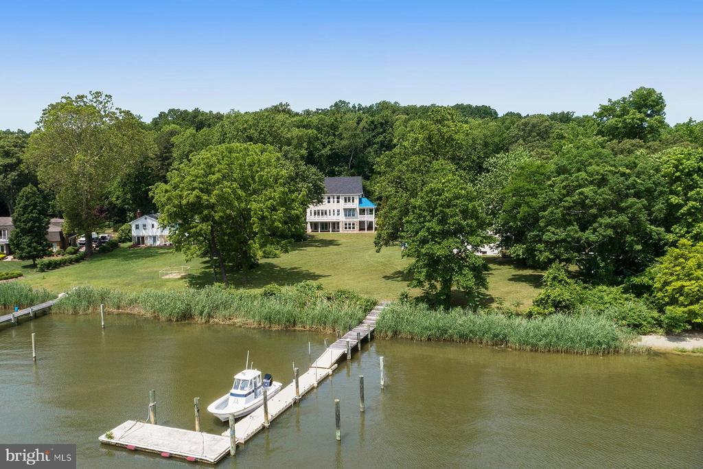 489 Edgewater Road is a BRAND NEW waterfront home located in Lake Shore on the widest part of the Magothy River, allowing for big views and deep water access. This five-bedroom, five-bathroom home is situated on a private almost acre lot in a blue ribbon school district. Sit back and watch the sailboat races from your raised waterside deck or hop in your boat and take a short ride out to the Chesapeake Bay. The community of North Shore offers a lot of activities for members and has a lot of amenities, including a beach, playground, picnic area, and boat ramp. The main level of the home has a gorgeous great room that looks out to the water through a wall of glass. The propane fireplace is a focal point that provides the perfect ambiance for chilly winter nights while still enjoying the water views. The great room flows into the gourmet kitchen with a HUGE center island complete with granite counters and a breakfast bar. Friends will admire the coastal feel of the white cabinetry and the stainless steel appliances, and everyone - including the chef - will appreciate the natural light and views. There's also a generously sized formal dining room. The main level includes a bedroom with a full bathroom; perfect for guests or as a home office! The lovely foyer is flanked on one side by a mudroom, with built-in storage. The master bedroom suite, located on the upper level, offers a spa-like setting.  The private waterside deck off the bedroom is perfect for taking in the views, having your morning coffee, or sipping on your favorite drink in the evening. The spacious master bathroom has a double-bowl vanity, granite countertops, oversized jetted soaking tub, and a tiled walk-in shower. Beyond is the walk-in closet.  The second bedroom has water views and an en-suite bathroom.  Two additional bedrooms share a full bathroom.  The walk-out, lower level game room offers tons of additional living space and includes a propane fireplace and a wet bar. This space is perfect for entertaining family and friends and provides access to the stone patio. There is also a full bathroom on this level. From the game room, stroll down to the water's edge. While there is not currently a pier on this property, the seller has obtained a pier permit. It's hard to find a brand-new waterfront home of this quality, within commuting distance to Baltimore or Washington!