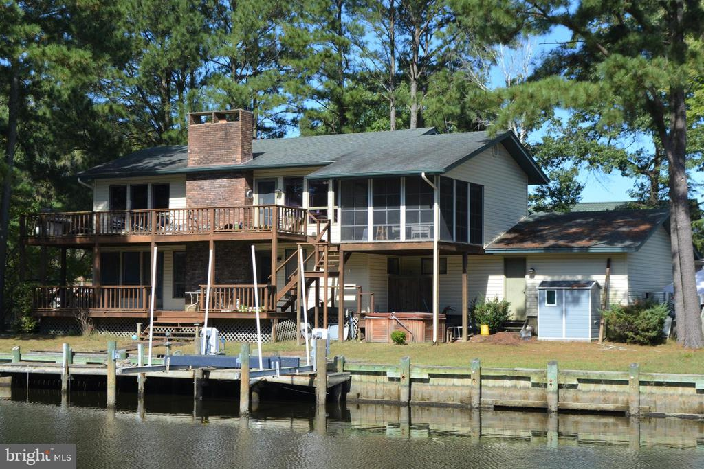 Unique waterfront home overlooking the 10th tee of the Ocean Pines golf course.  Spacious decks and 3 season porch have gorgeous views of both the waterway and fairway.  The home has a large 1/2 acre yard and over 200 feet of bulk-headed waterfront with dock and boat-lift. Two open living rooms, each with its own wood-burning fireplace and two master bedrooms, can accommodate your guests. Upgraded kitchen and dining room have brilliant views of the waterway and golf course. Downstairs living room includes a wet bar for entertaining.  Hot tub, outdoor shower and garage with workbench. Home was appraised in April 2018 at $508,000! Encapsulated crawl space with dehumidifier. Dual zone HVAC. 1 year HMS Home Warranty. Walk to the Ocean Pines Golf & Country Club!