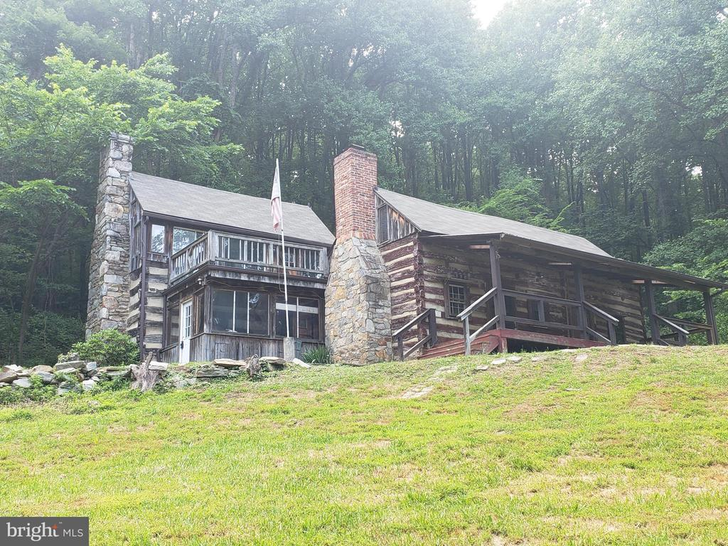 Price Reduced!!!  Make us an OFFER!~  REHAB or DEVELOPMENT OPPORTUNITY!  Unique LOG Home situated on priv. 8.49 Mountainside Wooded Ac w/Old Spring fed Pond, Lg Storage Shed.. Run-In type. All Selling AS-IS. Design potential enormous! There are also 2 addtl subdivided connected raw land parcels available- priced separately or BUNDLE ALL 3 for BETTER PRICING!  BUILD to SUIT!   2 out of the 5 total parcels are already sold. 2 neighboring custom homes coming soon.~  The 4.3 ac; 6.68 acres are still available to purchase and built your dream home.  Seller not responsible for rollback taxes. COMMUTERS...Minutes to Marc Train!