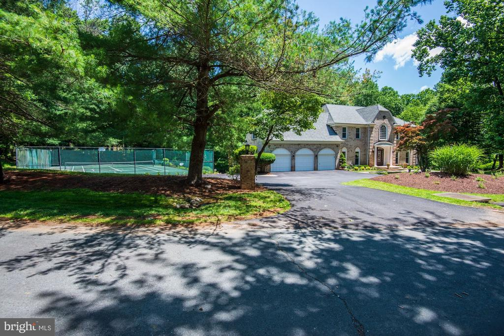 **New Price / Motivated Seller**Exquisite All Brick Colonial on a 2 acre setting located close to Congressional Country Club. A fabulous floor plan for both full size entertaining and comfortable family living, which features high ceilings, and hard wood floors through out. The main level has an updated gourmet kitchen with custom cabinets, designer stone counter tops. Subzero, Viking and Wolfe appliances. There is an adjoining breakfast room, with an additional family room area that over looks expansive decks and Tennis court. The formal living and dining room features crown moldings, hardwood floors, along with a private library with built in bookshelves. Enhancing the homes appeal is an Embassy size entertaining room with bar and beautiful stone fireplace. The upper floor host a stunning deluxe master bedroom suite, a large sitting area, along with an oversized bath and closets. There are 4 additional bedrooms that complete the upstairs level. The fully finished lower level has high ceilings, family room, game room,  a 6th bedroom or guest suite/office with a luxury bath. In an addition to an attached 3 car garage the home has multi-level decks with views of a private backyard, a 2 acre lot, and a tennis/sports court. Ideally located one mile from the Capitol beltway, this home is convenient to shopping, restaurants, public parks, 2 major airports and a short drive to Bethesda, DC, Tyson Corner and Montgomery Mall Open House 7/21 1-4