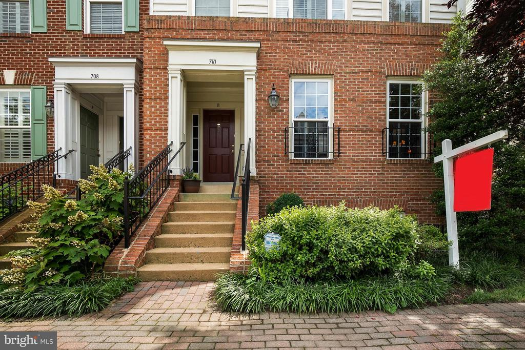 Bright and sunny 2 level townhouse style condo in the friendly Old Town Greens community.  Large kitchen has been upgraded with granite counter tops and stainless steel appliances. Hardwood floors through out both levels. Covered rear deck is great for grilling and dining. Amazing storage space. Private garage with additional parking space in driveway. Great community amenities including pool, playground, tennis courts and transportation to Braddock metro. Water, trash removal, and landscaping included. Convenient location makes for an easy commute - Only 2 traffic lights to DC. Minutes from national landing (new Amazon HQ) and upcoming Potomac Yards Metro station. Three miles to Reagan National Airport. Walk to Old Town and Del Ray shopping and dining.