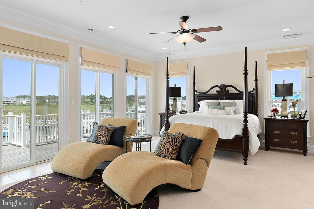 Finest Luxury Living! Waterfront expansive home with boat slip for discriminating owner and anglers alike. Perfect for those who love to entertain & want to live the coastal marina lifestyle. Windows and sliders galore which allows for spectacular views and lots of natural light. Five spacious bedrooms, den & library each w/windows and/or own balcony overlooking Ocean City lights, the bay, inlet and marshes. This home sets the stage for amazing views, sunsets and watching boats and yachts. The first floor offers guest quarters or an in-law suite: Generous size Captain~s Galley, four bedrooms, 3 baths, den, laundry and own HVAC zone. Take elevator up to the Living Level: upgraded kitchen along with an incredible open-concept great room that includes dining room, sitting area, living room & bar, powder room & laundry w/storage and own zone. Make your drink of choice at your bar and sit on balcony to watch the ~sun~sational sunsets over marina. The next level, The Owner~s Suite boasts water views from the wall of windows in the master suite w/sitting areas-imagine waking up looking out those windows. There are also even views from the incredible dressing lounge and gorgeous bath. If you need to step away to work from home, there is a library with own powder room overlooking the bridge and of course own zone. To round out this fantastic home, ride the elevator to the top floor and step out onto the Crow's Nest overlooking deep water slip and views of Ocean City and Marinas. This area is made for watching the White Marlin participants, the Air Show and Fireworks at the Inlet. Two car garage provides extra storage for water toys and golf clubs and leads into the mud room. If you happen to have a larger yacht or want to dock jet skis in addition to your boat, the marina in next door. They can house boats larger than 42 ft. Plus there are some great new restaurants, all only a stroll away. And shopping and new movie theater across street. This home is one of a kind and well suited for anglers, marine & beach enthusiasts alike. Upgraded window treatments, ceiling fans, wood flooring and finishes.  3-Zone system. Slip #13 conveys.Schedule private showing today.