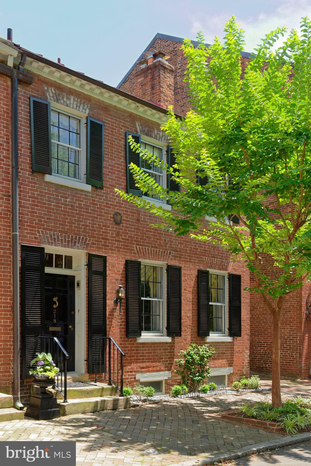 218 South Royal Street enjoys a storied provenance and prime location right in the heart of Old Town. Built in 1800, by Reuben Johnston, who built 214, 216 and 218 South Royal, the charming brick home sits on one of Alexandria~s original town lots, 1 1/2 blocks off King Street, a commercial street since the 1800's.218 is the largest of the 3 houses and the only one that~s semi-detached, now with parking on the south side. It is also one of the first thousand houses in Alexandria with running water! Back in the day, a stable was situated behind 218 and 216. Horses walked down the path between 218 and 220 (now a side garden/inner courtyard for 218 plus off-street parking) to access the stable in the rear.One of the early owners of 218, circa 1844, was William Wallace Adam, a silversmith. With its rectangular shape and 2 stories, the house exemplifies the Federal style of the 1820-1830's, but its dentil cornice along the roof line and transom ornamentation above the entry door are reflective of the Georgian period of architecture. Lovely flower boxes line the windows, graced by classic shutters. Many original details of this gem include an original front staircase, original floors throughout, original solid 6-panel entry doors and casings in the living and dining room,plus 2 original fireplace mantles in both rooms supported by reeded pilasters. Old meets new in the recently renovated eat-in kitchen with wood cabinetry, a furniture island, copper sink, and bow window facing the inner courtyard with fountain. Adjoining is a sunny family room with built-in wood cabinets flanking the raised fireplace, and a full bath. A small light-filled room with skylights and 3 windows beyond the family room, perfect as an office,overlooks the pool and plantings. Upstairs await 4 spacious bedrooms and 3 full baths. The master suite has a fireplace,window seat, his and her bathrooms, and separate newer private staircase to the first floor. Storage is very extensive for a historic home. 