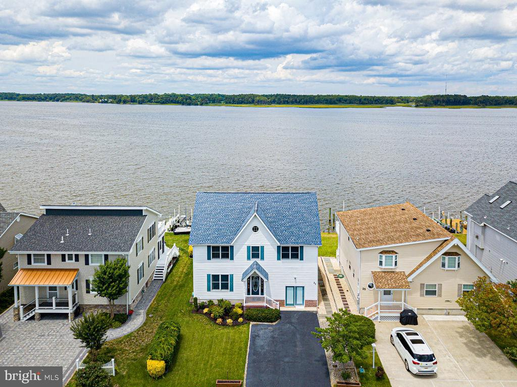 Direct Waterfront home offers magnificent panoramic views of the open water, and views of the sunrise and sunsets. This home is well cared for by long time owner and offers 4 bedrooms and 2 1/2 baths. There is a large sunroom and rear deck for you to enjoy and great for entertaining. Boat dock with boat & jet ski lifts for summer fun. The bulkhead is maintained by the Ocean Pines Association. The kitchen features a large walk in pantry, water views and access to the rear deck which makes grilling easy. 3 bedrooms are located on the water to take advantage of the views. Features include an open floorplan, gas wood stove, Andersen windows, double sinks and ceramic tile shower in Master Bath. A 2nd family room is located adjacent to the 4th bedroom (great for kids to have their own space). There is a storage room for your bikes, fishing rods, boating gear and beach chairs. The roof is 3 years old, and the refrigerator, range and microwave are only a few years old. Owner will provide a one year warranty to buyer. Enjoy all the community of Ocean Pines has to offer including Yacht Club and restaurant, 5 swimming pools (1 enclosed), Robert Trent Jones golf course, marina, Community Center, Beach Club on the ocean, community police and fire departments, skate park, dog park, playgrounds, walking / biking trails, indoor gym, racket center with 8 pickle ball courts.